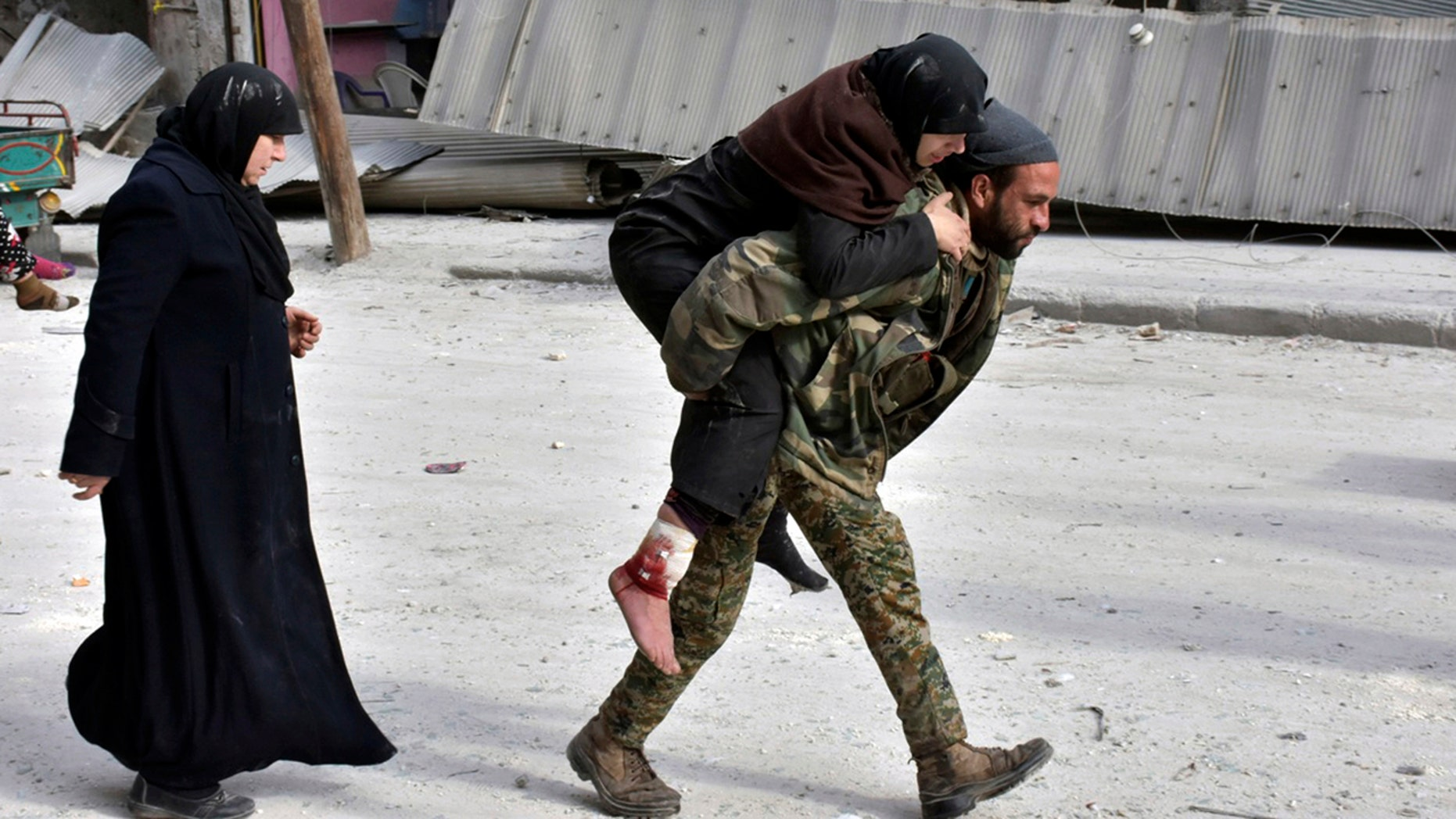 Dec. 12, 2016: In this photo released by the Syrian official news agency SANA, a Syrian soldier carries a wounded woman in eastern Aleppo.