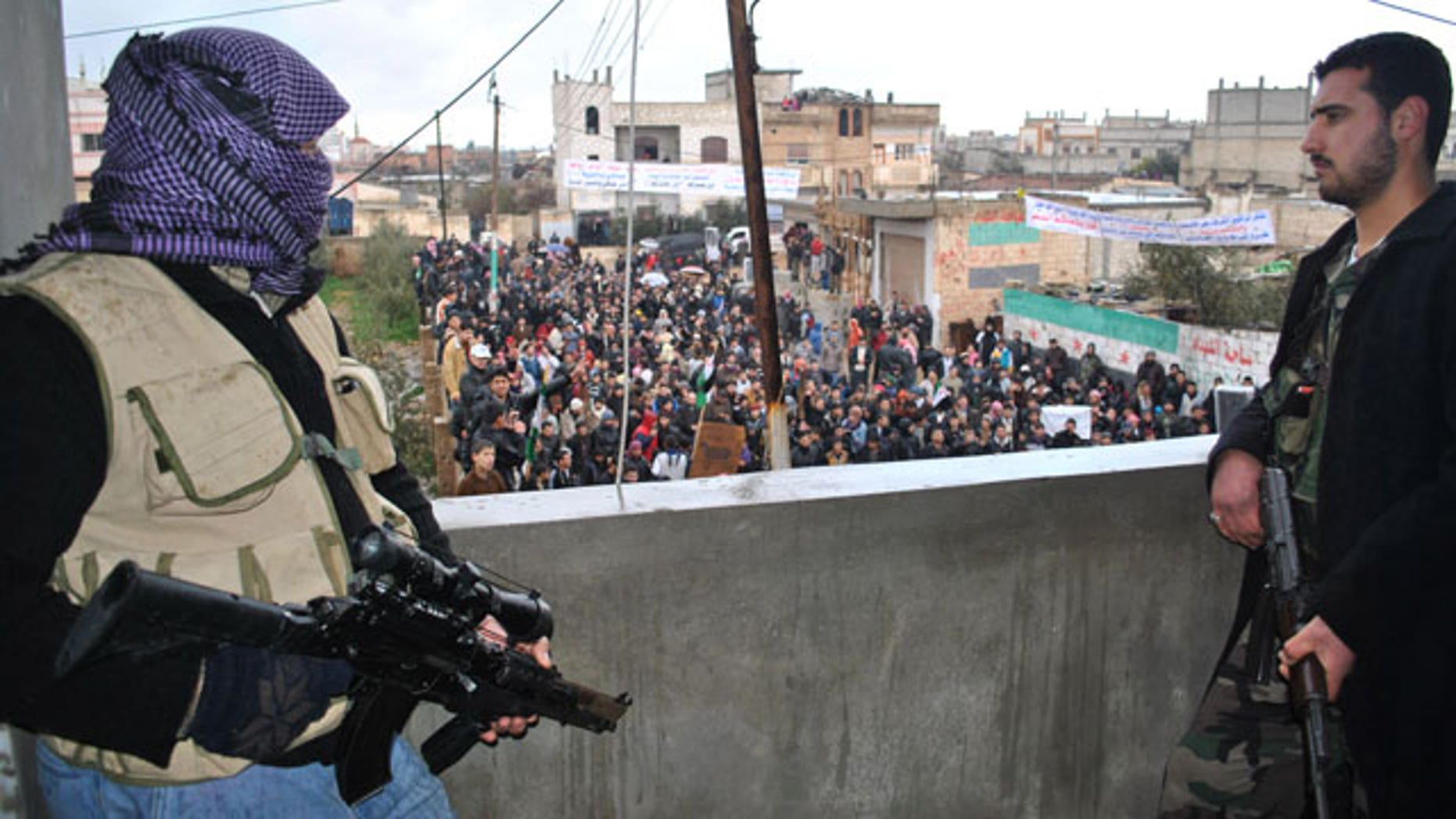 Jan. 27, 2012: Syrian army defectors stand guard on a rooftop to secure an anti-Syrian regime protest in the Deir Baghlaba area in Homs province, central Syria.