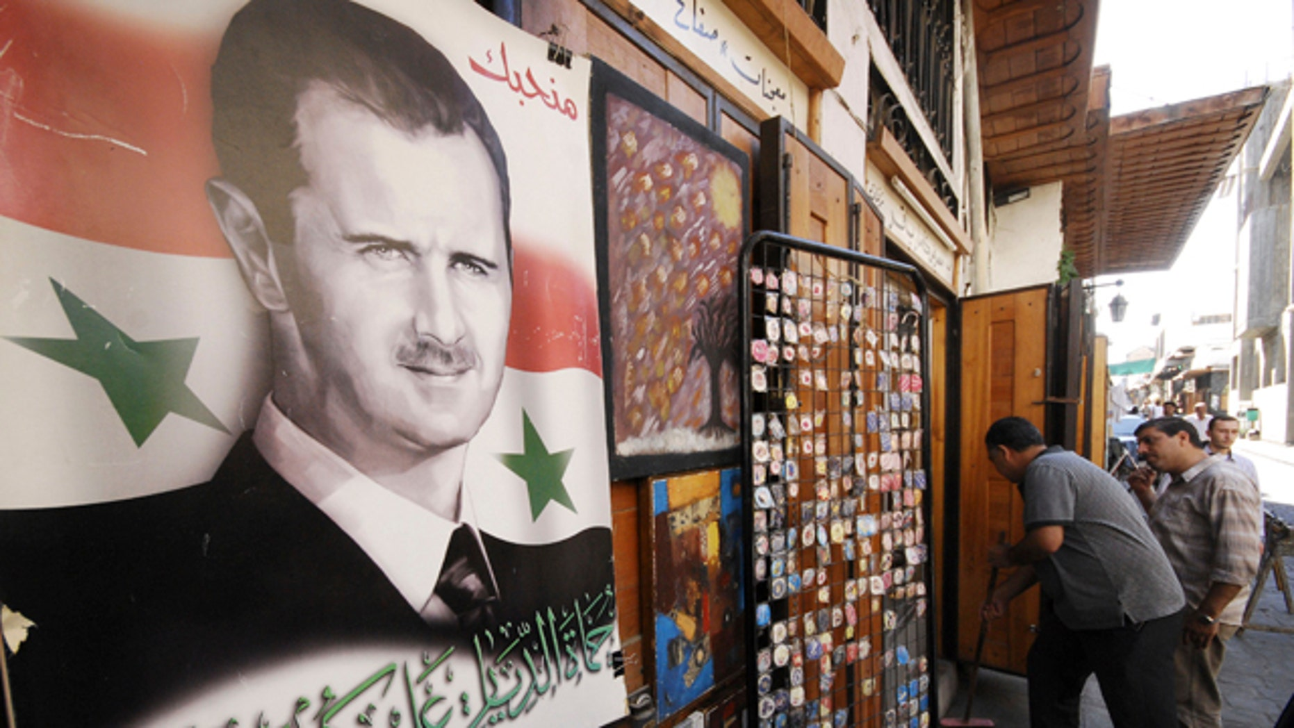 """Sept. 15: A Syrian man cleans while attached to his shop is a portrait of Syrian President Bashar Assad with Arabic words reading: """"We love you, Welders homes peace on you"""" in Damascus, Syria."""