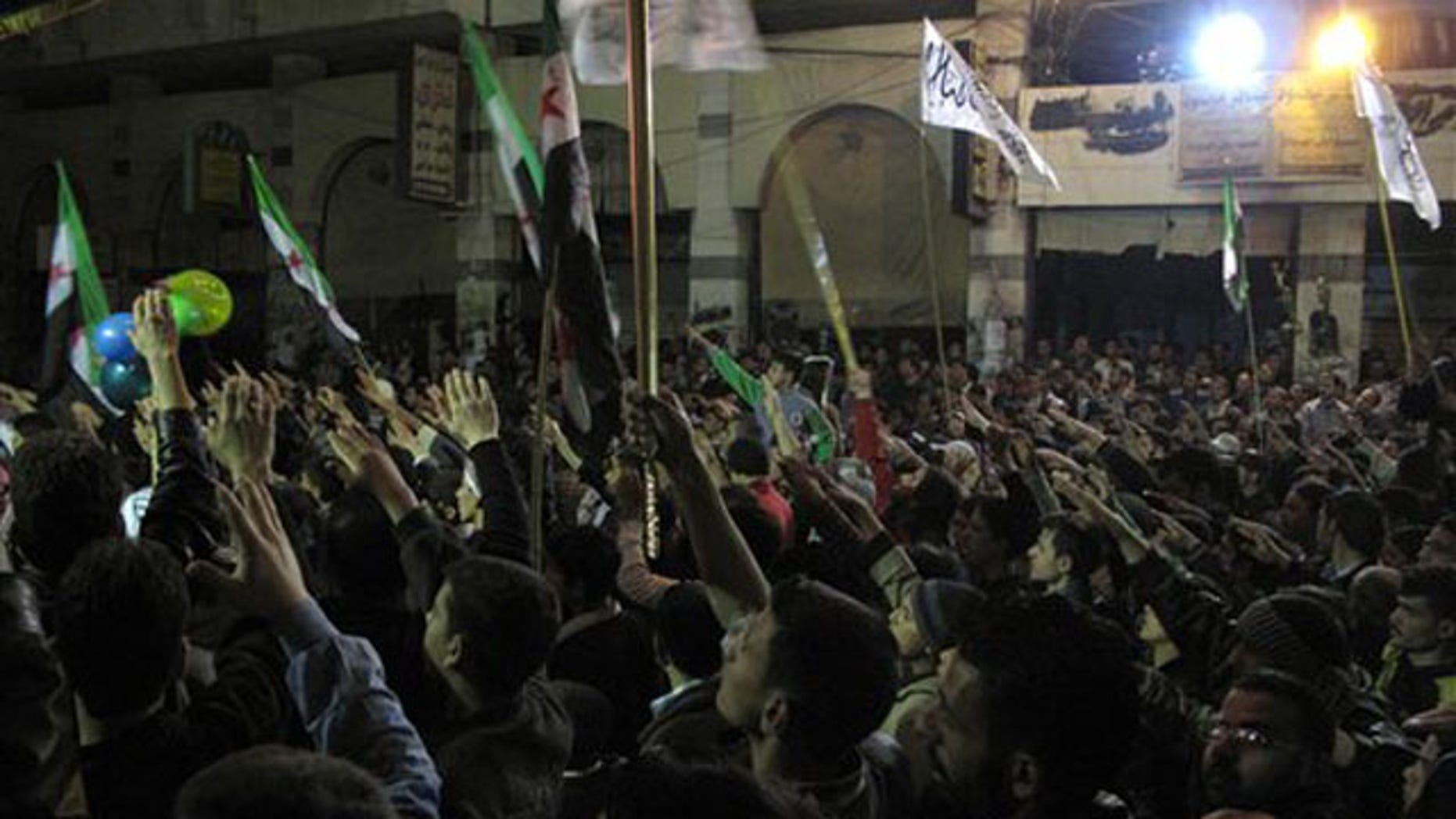 April 4, 2012: In this photo, Syrians raise their hands vowing to continue fighting until President Bashar Assad's regime falls during a protest in a neighborhood in Damascus, Syria.