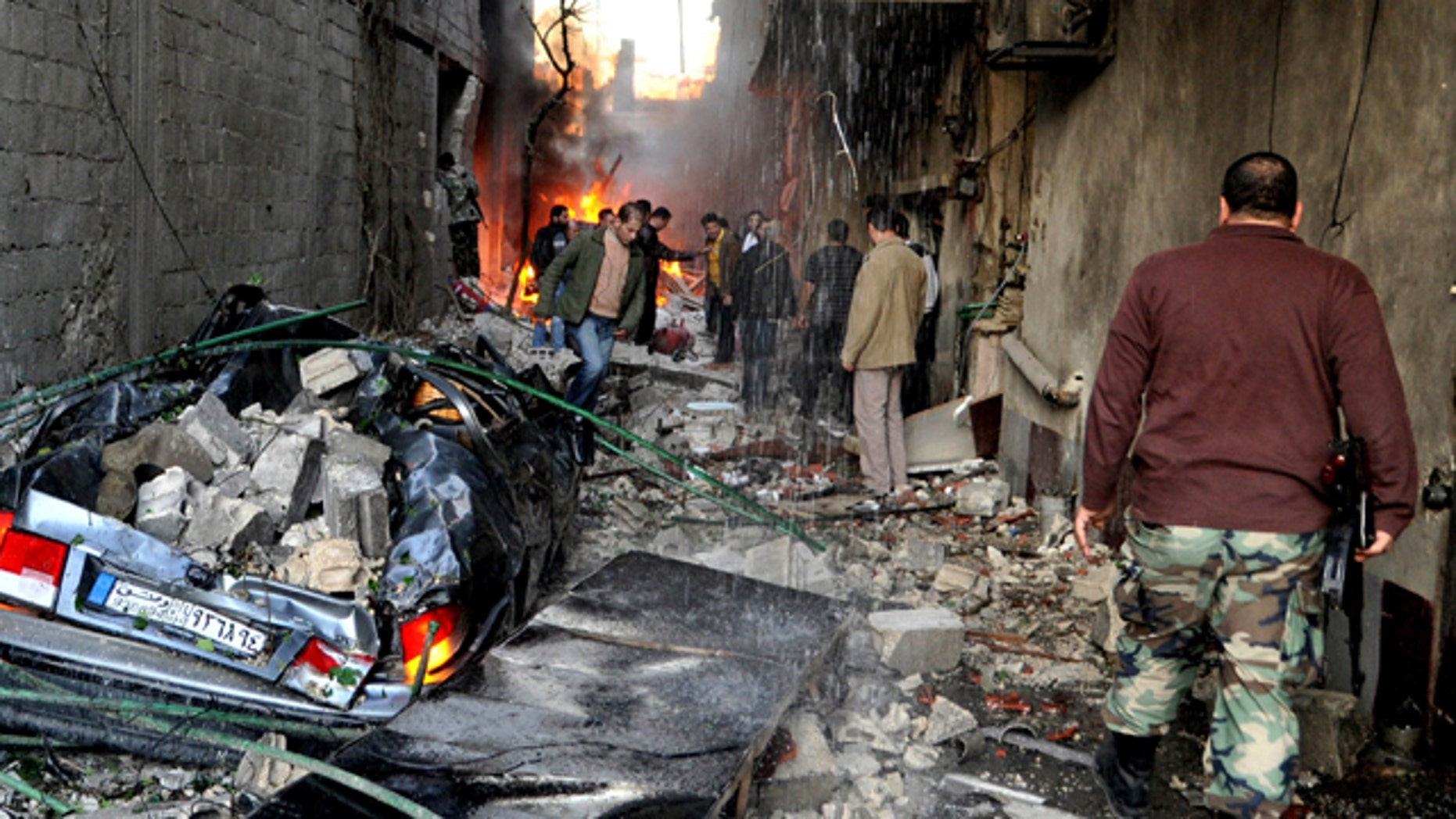 Nov. 28, 2012: A Syrian soldier, right, and citizens gather at an alley that was destroyed by two cars bombs in a suburb of Damascus, Syria.