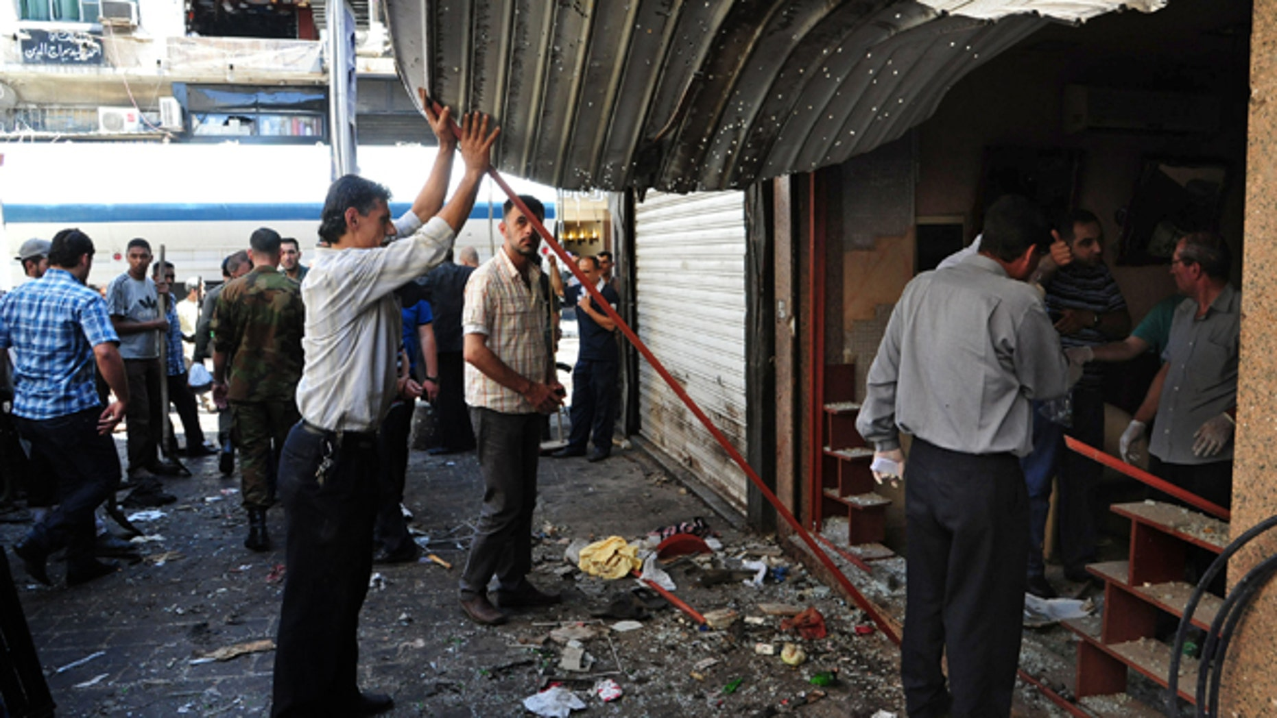 June 11, 2013: In this photo released by the Syrian official news agency SANA, Syrians inspect a damaged shop at a scene of two explosions in the central district of Marjeh, Damascus, Syria.