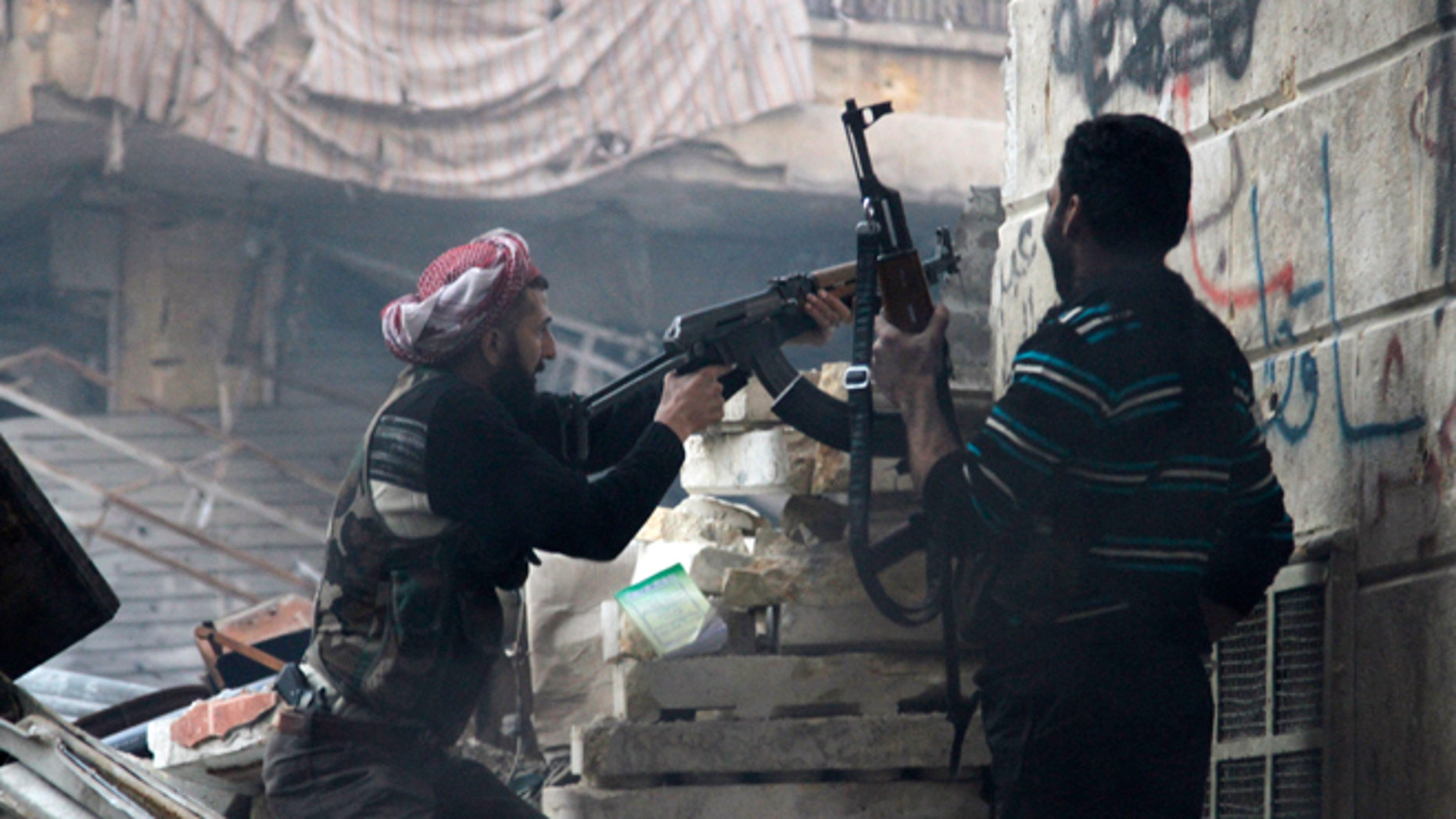 FILE: Dec. 29, 2012: Free Syrian Army fighters fire at enemy positions during heavy clashes with government forces, in the Salaheddine district in Aleppo, Syria.