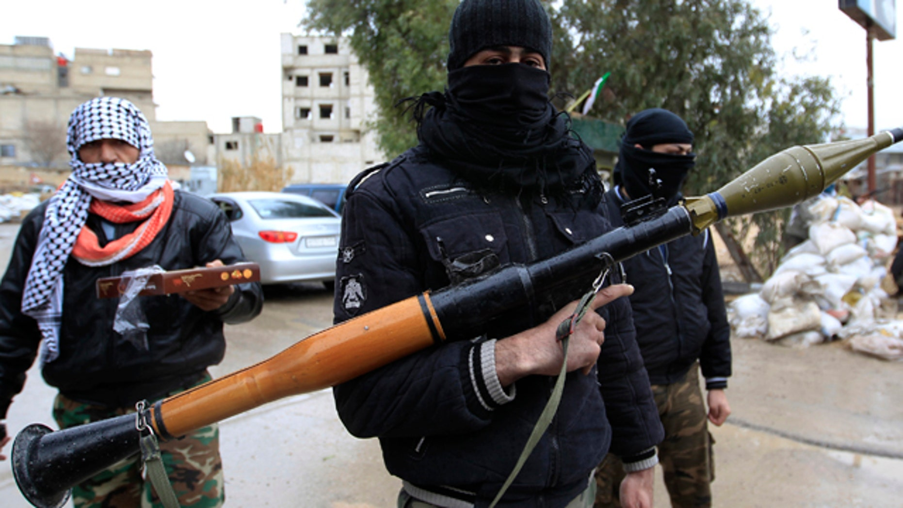 Jan. 27: Syrian soldiers, who have defected to join the Free Syrian Army, look on as one holds up an RPG and another delivers sweets in Saqba, in Damascus suburbs.
