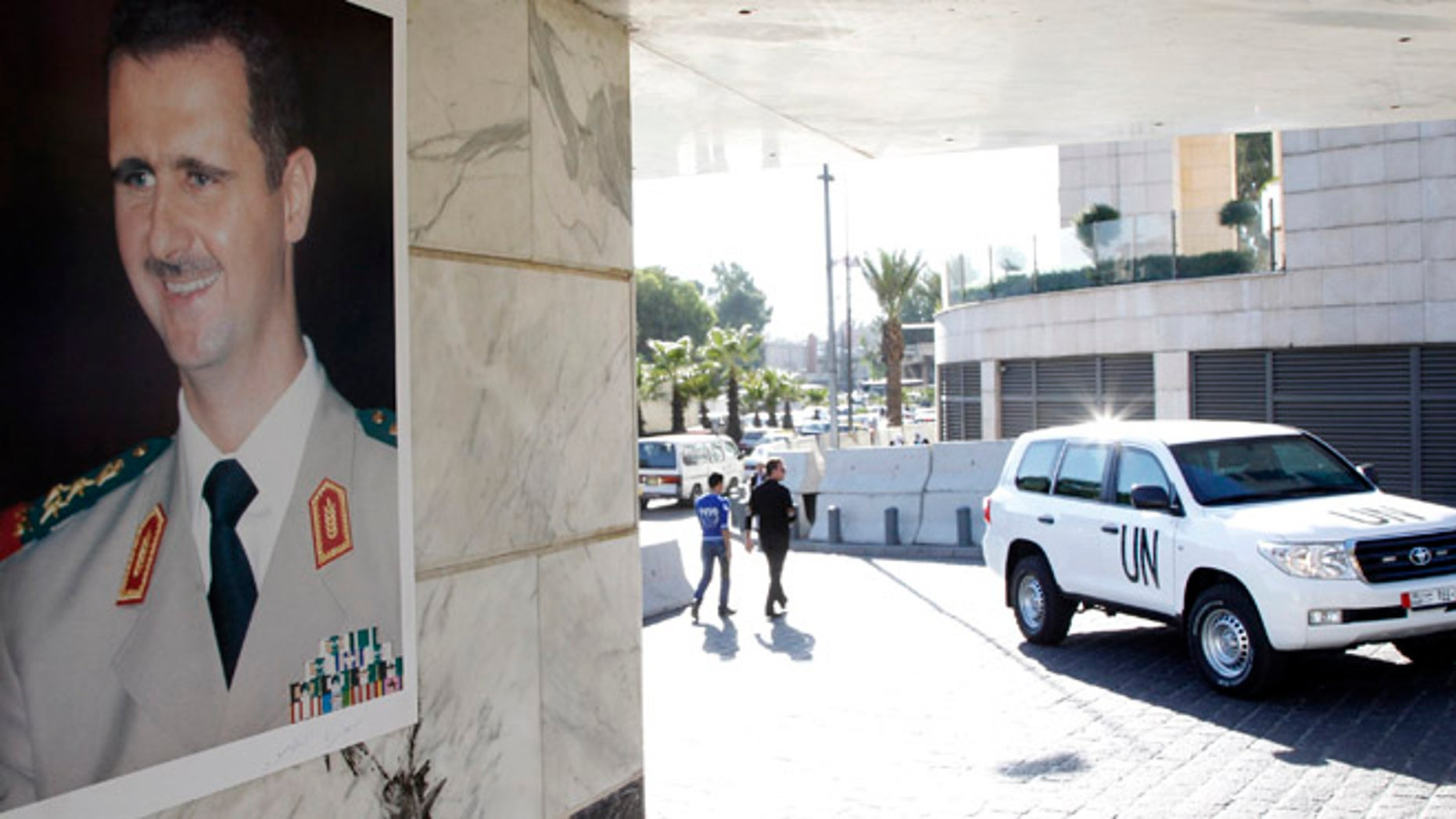 Oct. 8, 2013: A U.N. vehicle is seen near a photo of Syrian President Bashar al-Assad at the entrance of a hotel where a team of experts from the Organisation for the Prohibition of Chemical Weapons (OPCW) were staying in Damascus. (Reuters)