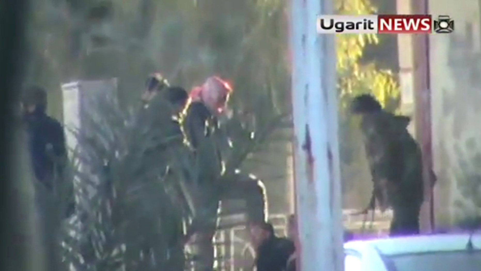 Dec. 12: This image from amateur video made available by the Ugarit News group purports to show a man being kicked by a group of soldiers in Hama, Syria.