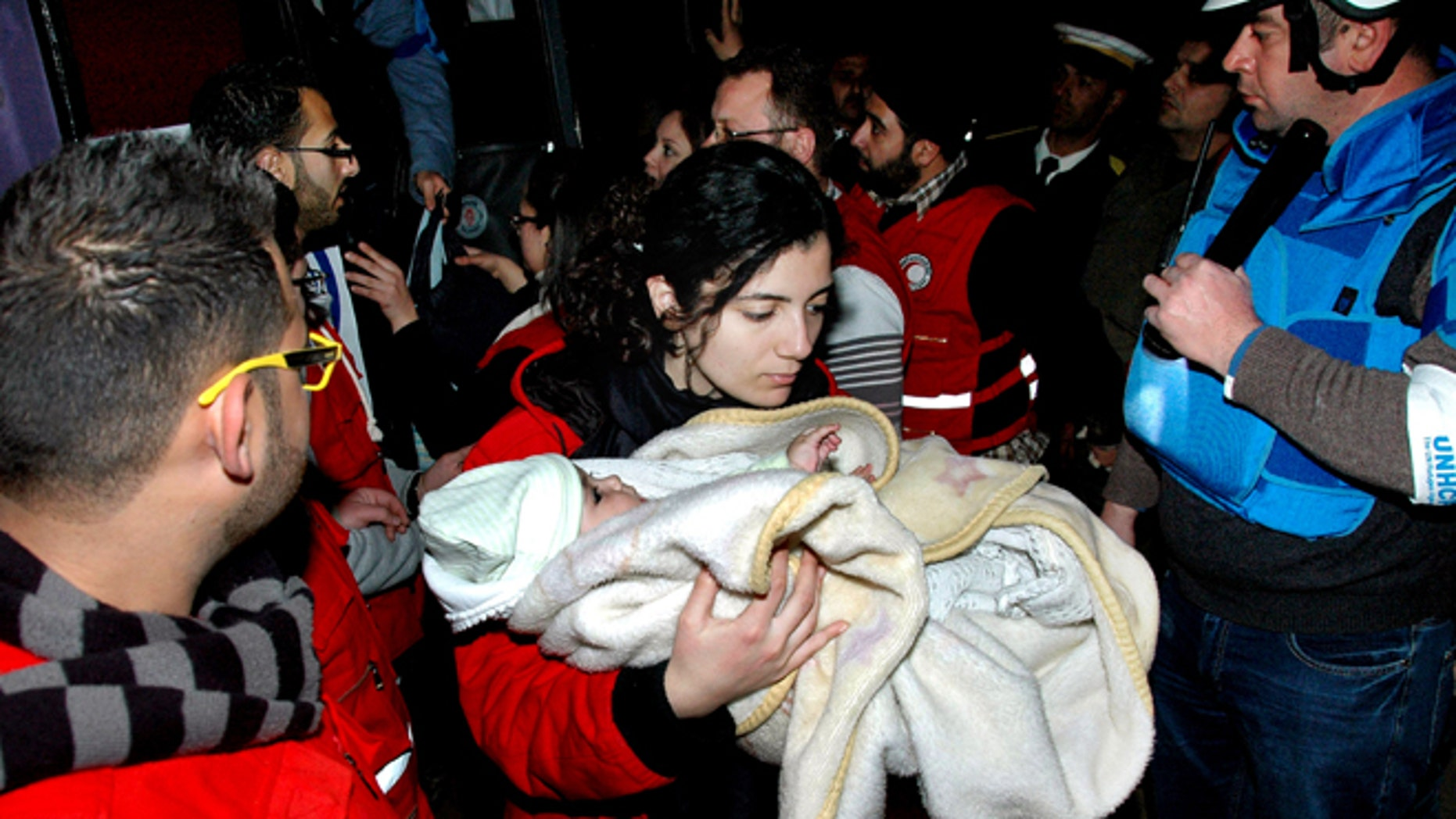 Feb. 10, 2014: In this photo released by the Syrian official news agency SANA, a Syrian Arab Red Crescent member in red uniform carries a baby on to a bus to evacuate the battleground city of Homs, Syria.