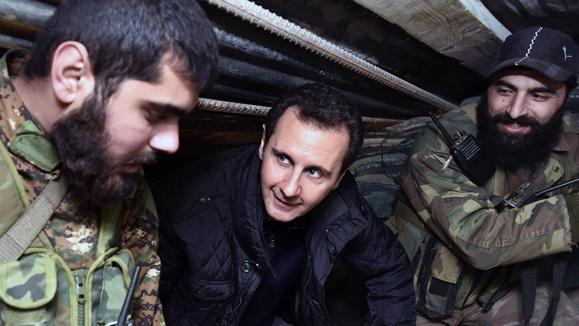 Dec. 31, 2014: Syrian President Bashar Assad, center, speaks with Syrian troops during his visit to the front line in the eastern Damascus district of Jobar, Syria.