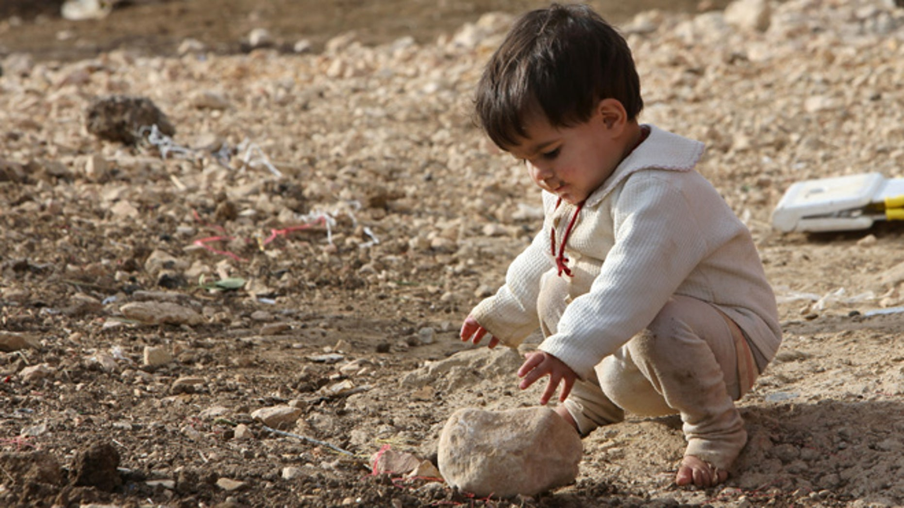 Nov. 5, 2013: A Syrian child plays with a stone at a refugee camp in Delhamiyeh village in the Bekaa valley, eastern Lebanon. There are more than 800,000 refugees registered with the U.N. refugees agency in Lebanon, but the Lebanese government estimates the real number of Syrians in the country at more than 1 million, or around one-third of the tiny countrys population.