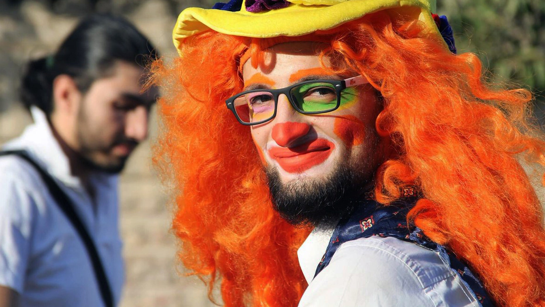 Syrian social worker Anas al-Basha, 24, dressed as a clown, while posing for a photograph in Aleppo, Syria.
