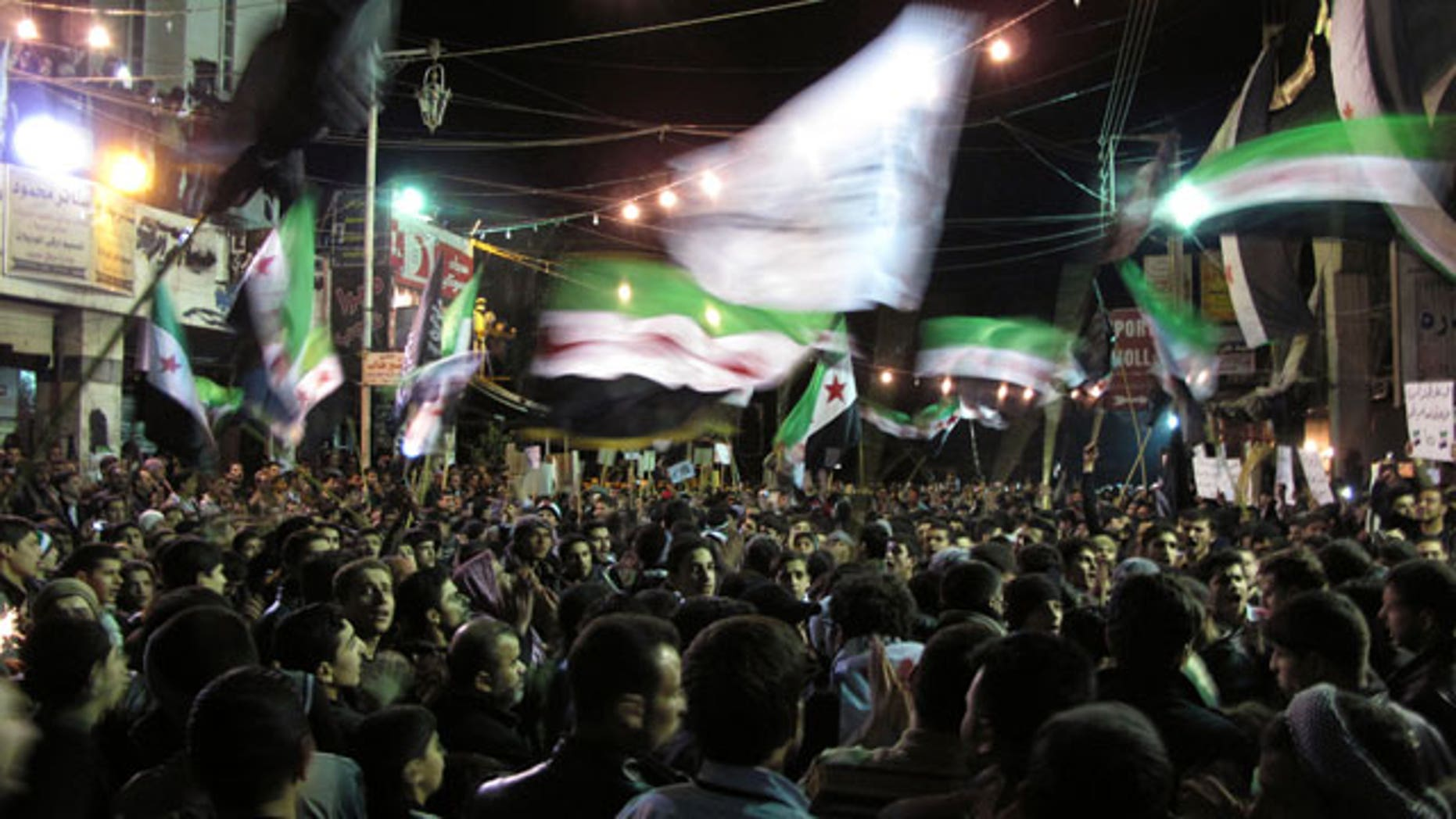 April 2, 2012: Syrians wave revolutionary flags and chant slogans at a night protest against President Bashar Assad in a neighborhood of Damascus, Syria.