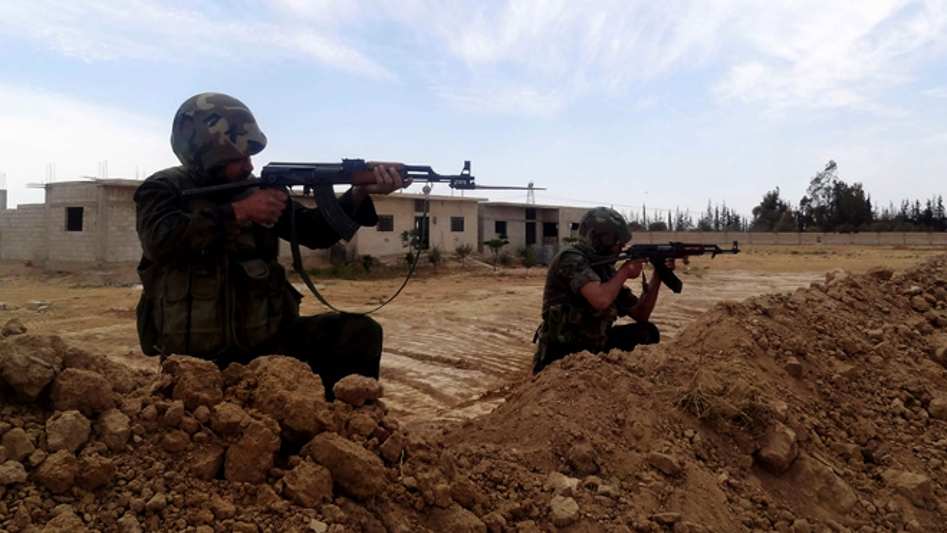 April 24, 2013: This photo released by the Syrian official news agency SANA, shows two Syrian Army soldiers aiming their weapons, in Otaybah town, east of Damascus, Syria. After five weeks of battle, Syrian government troops captured a strategic town near Damascus, cutting an arms route for rebels trying to topple President Bashar Assad's regime, state media and activists said Thursday.