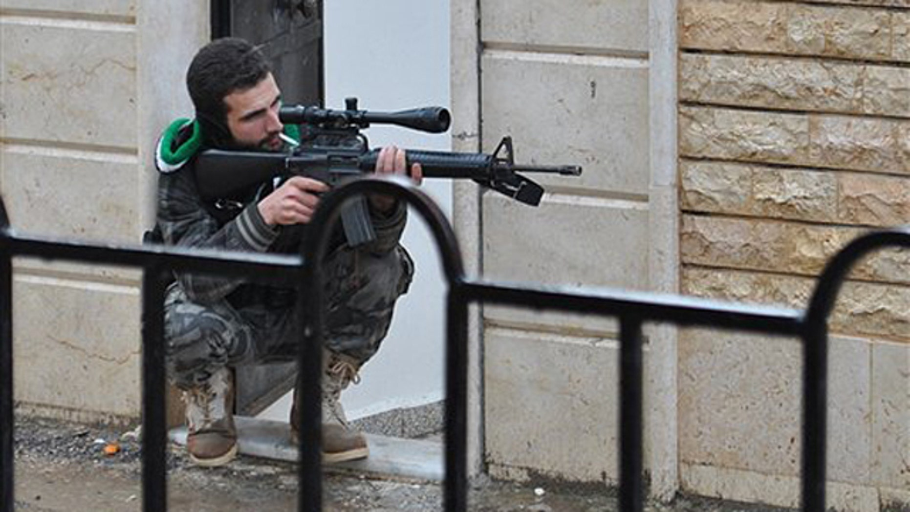 Jan. 31, 2012: A Syrian rebel takes his position as he points his gun during a battle with the Syrian government forces, at Rastan area in Homs province, central Syria.