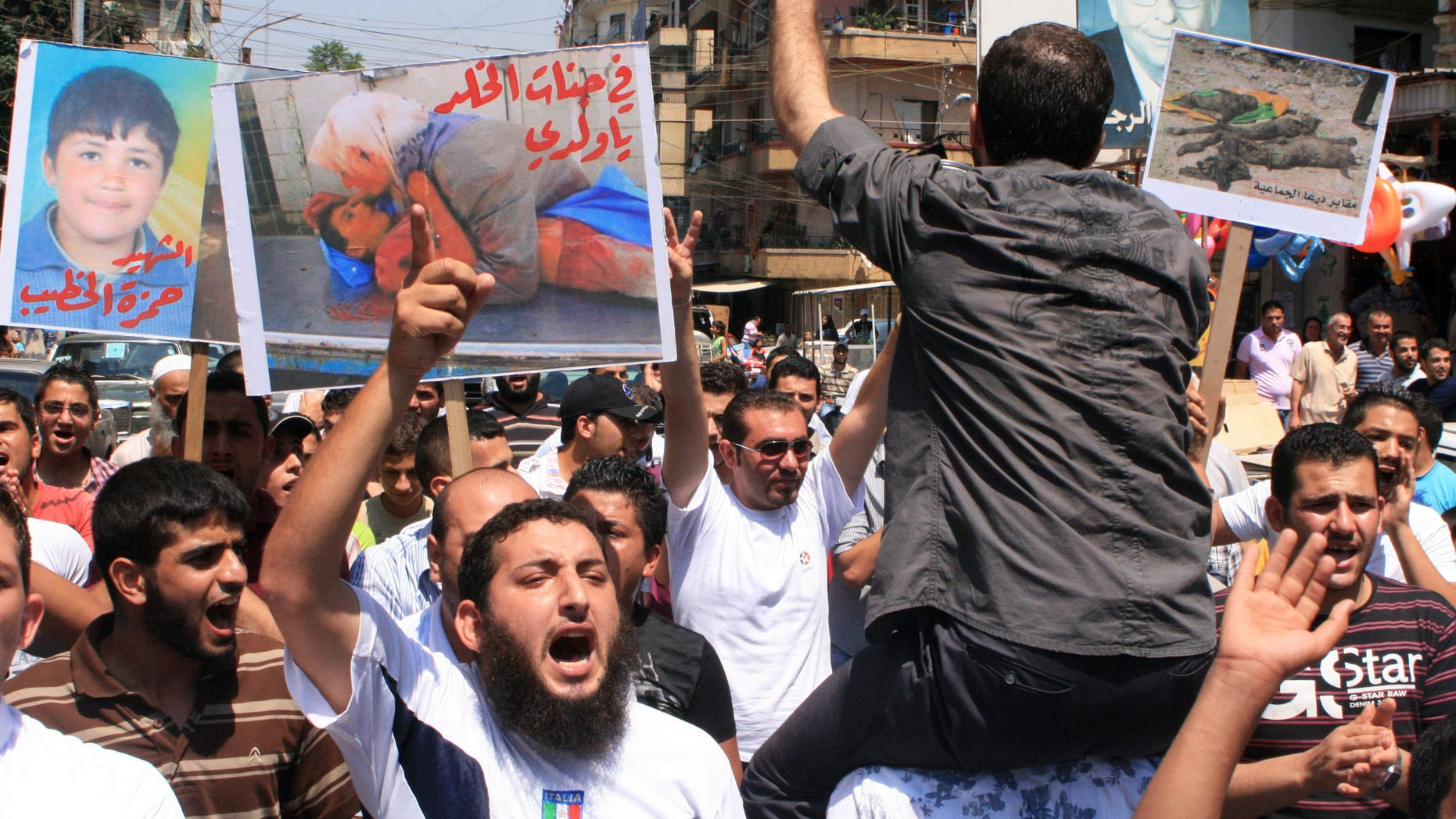 """Lebanese protesters shout slogans as they carry banners in Arabic that read:"""" you are in heaven my son,"""" center, """"the martyr Hamza el-Khatib,"""" left, and """" Daraa mass graves,"""" right, during a rally in solidarity with Syrian anti-government protesters in the northern city of Tripoli, Lebanon, Friday, July 15, 2011."""
