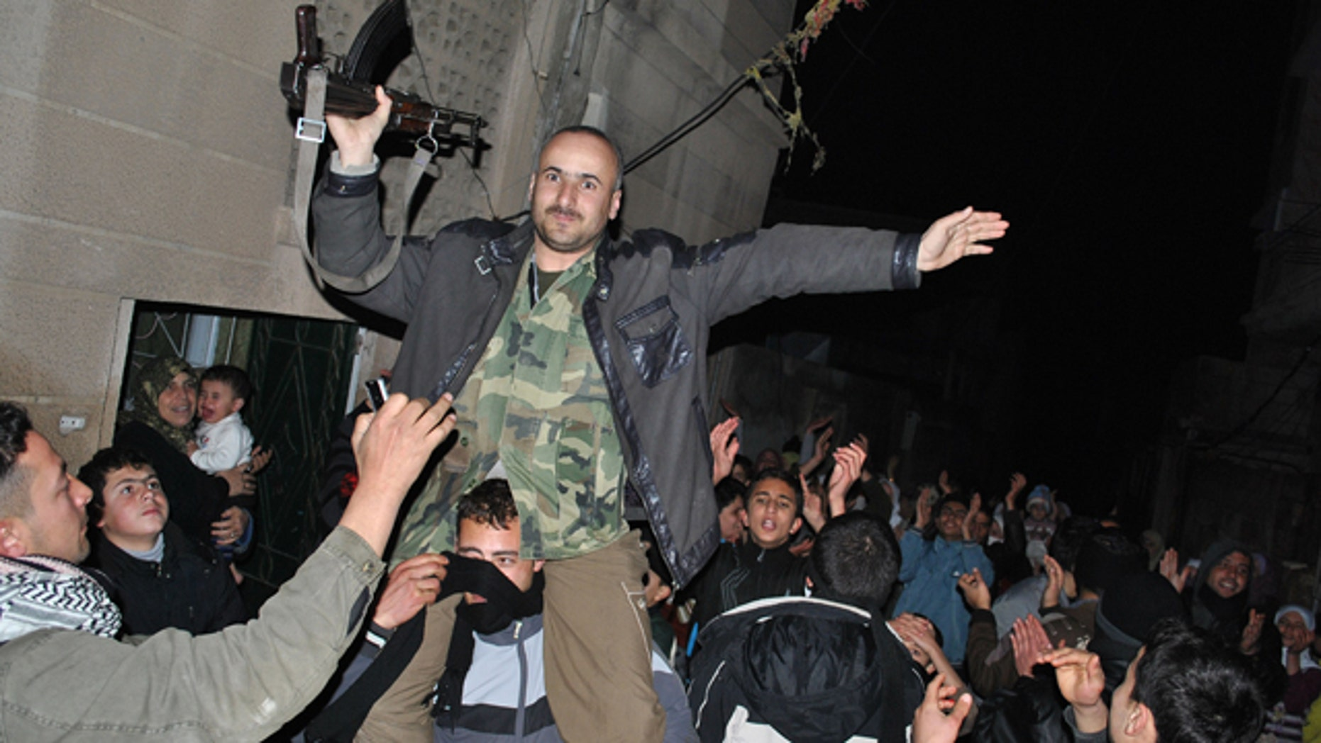 Anti-Syrian regime protesters, hold up a Syrian army defector as they chant slogans against Syrian President Bashar Assad during an evening protest, in the Rastan area in Homs province, central Syria, on Monday Jan. 30, 2012. Syrian forces heavily shelled the restive city of Homs on Monday, and troops pushed back dissident troops from some suburbs on the outskirts of Damascus in an offensive trying to regain control of the capital's eastern doorstep, activists said.(AP Photo)