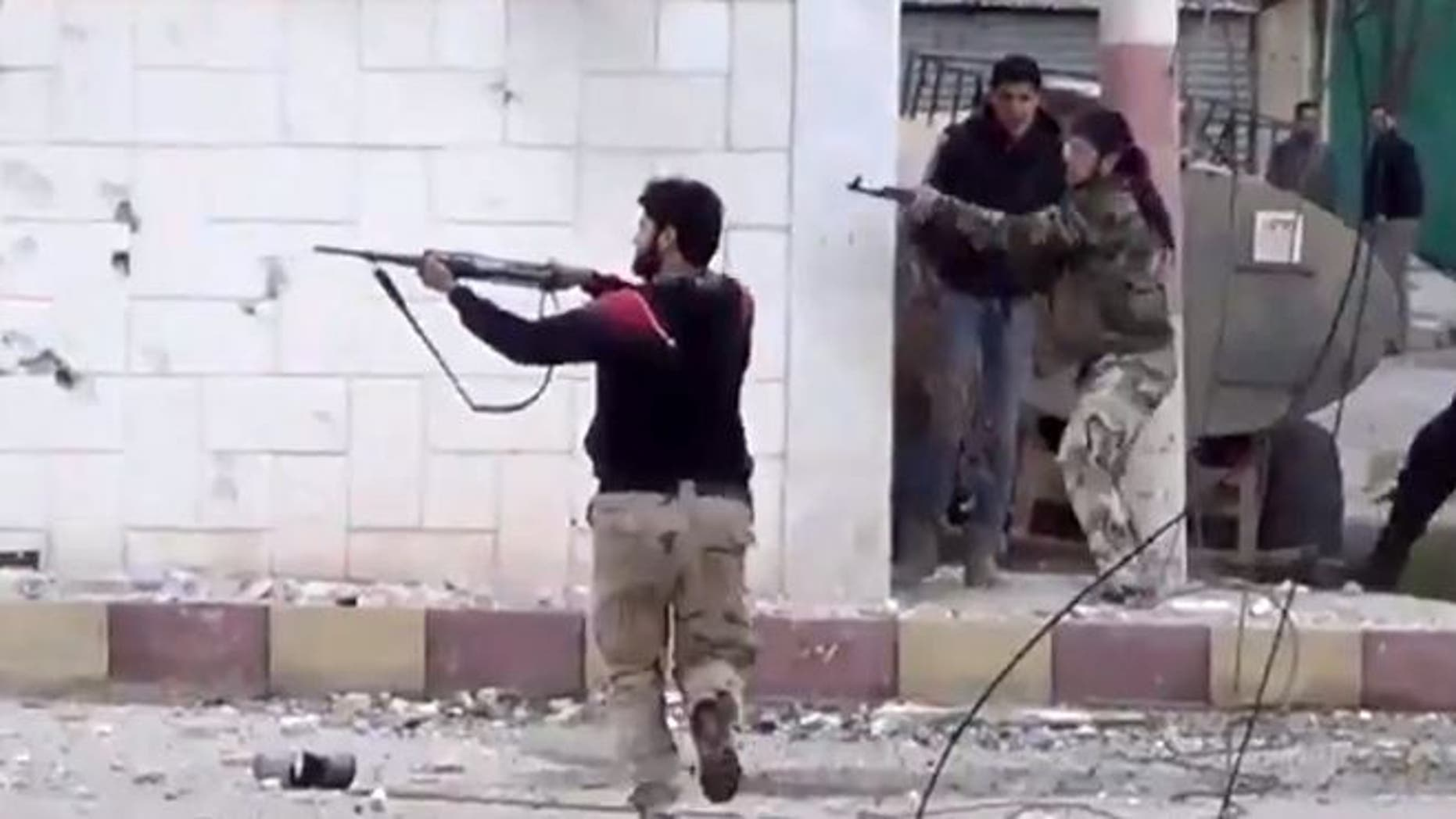 FILE: March 18, 2013: Free Syrian Army fighters fire at Syrian army soldiers during a fierce firefight in Daraa al-Balad, Syria.