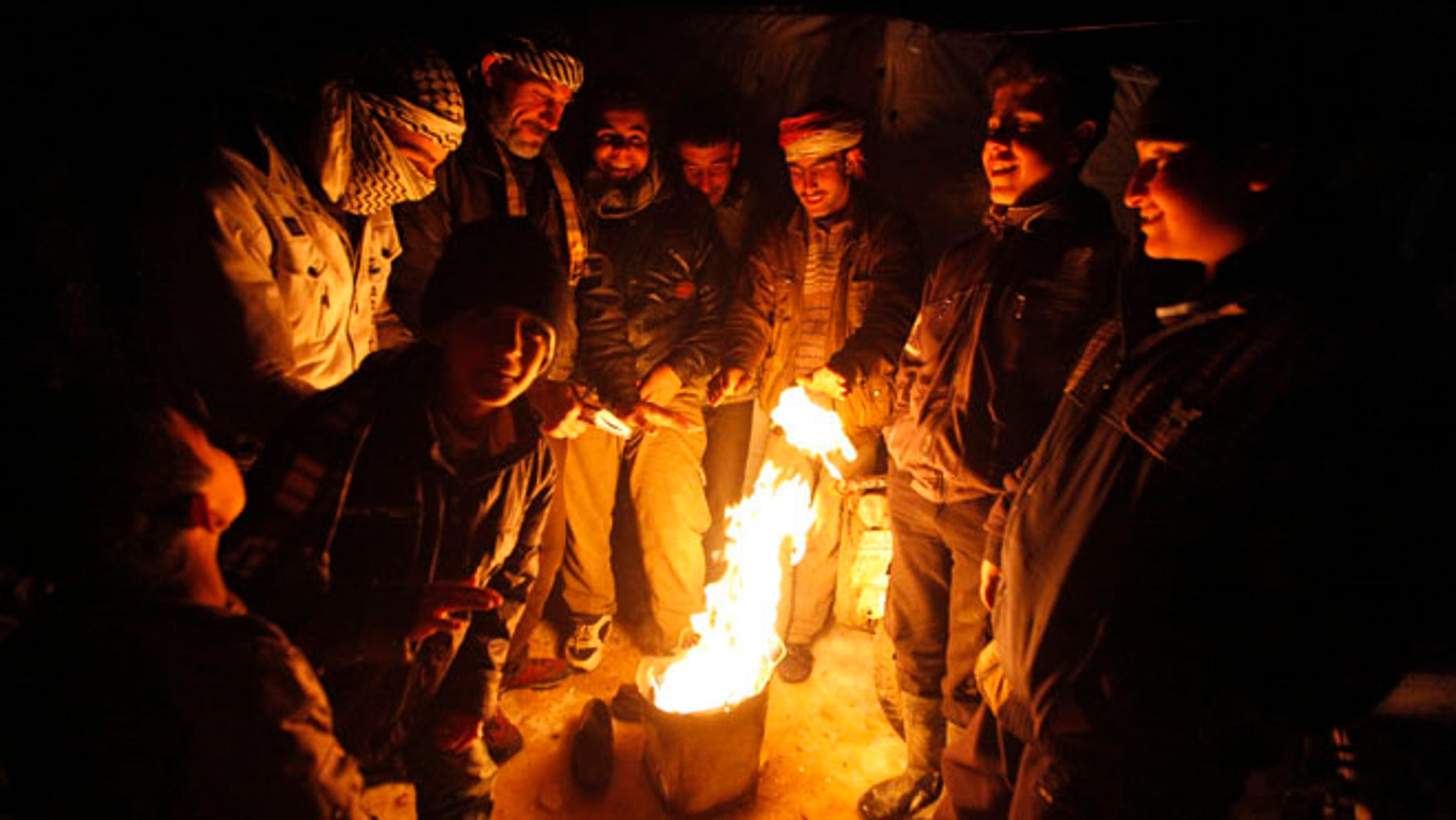 Dec. 12, 2013: Syrian refugees from the town of Qara gather around a fire to keep themselves warm in a Syrian refugee camp on the Lebanese border town of Arsal, in eastern Bekaa Valley. (Reuters)