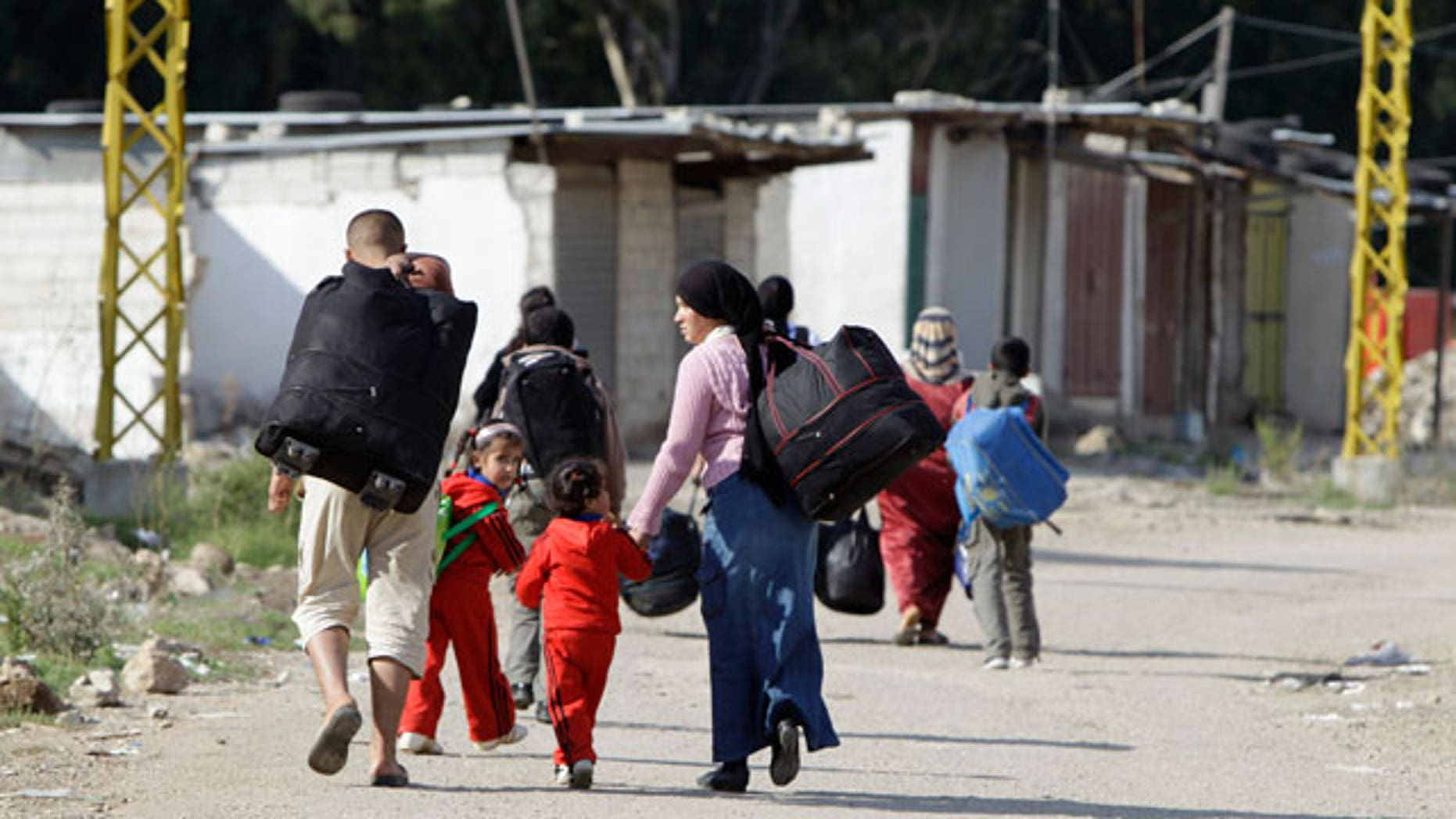 Oct. 31, 2011: Syrian citizens carry their belongings as they cross the Lebanon- Syria border illegally to return to Syria, from the village of Arida, north Lebanon.