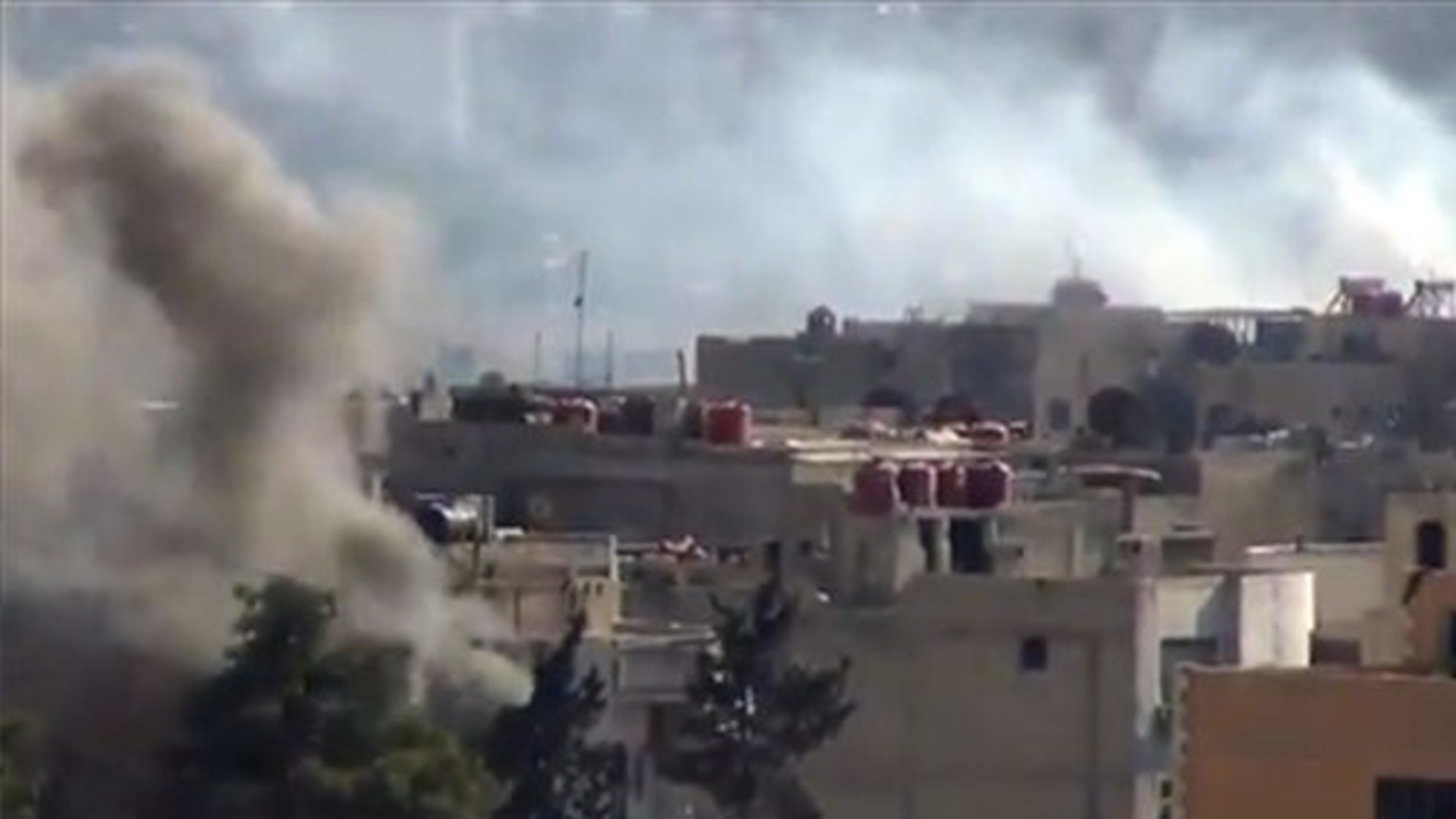 Sept. 4, 2013: Smoke rises from buildings due to heavy clashes between Free Syrian army fighters and government forces in Daraya, a suburb of Damascus, Syria.