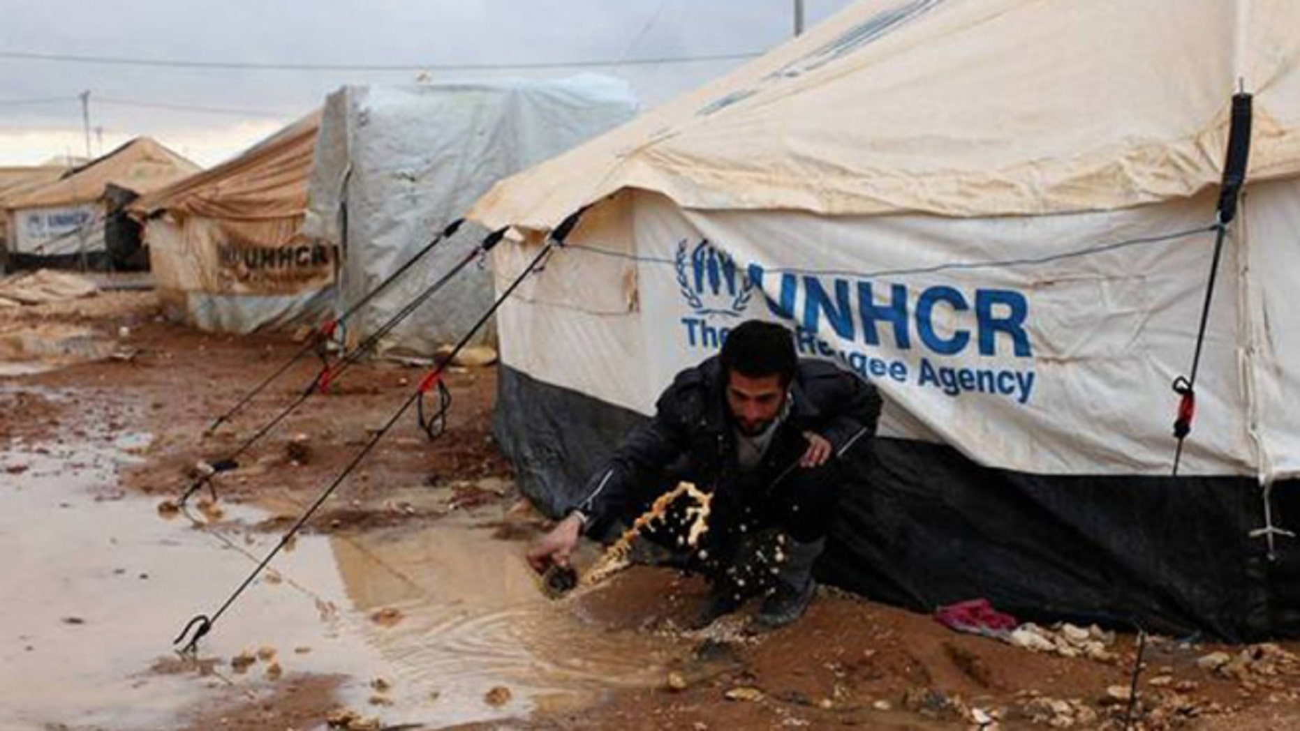 A Syrian refugee removes water and mud around his UN-supplied tent, at Zaatari Syrian refugee camp, near the Syrian border in Mafraq, Jordan.