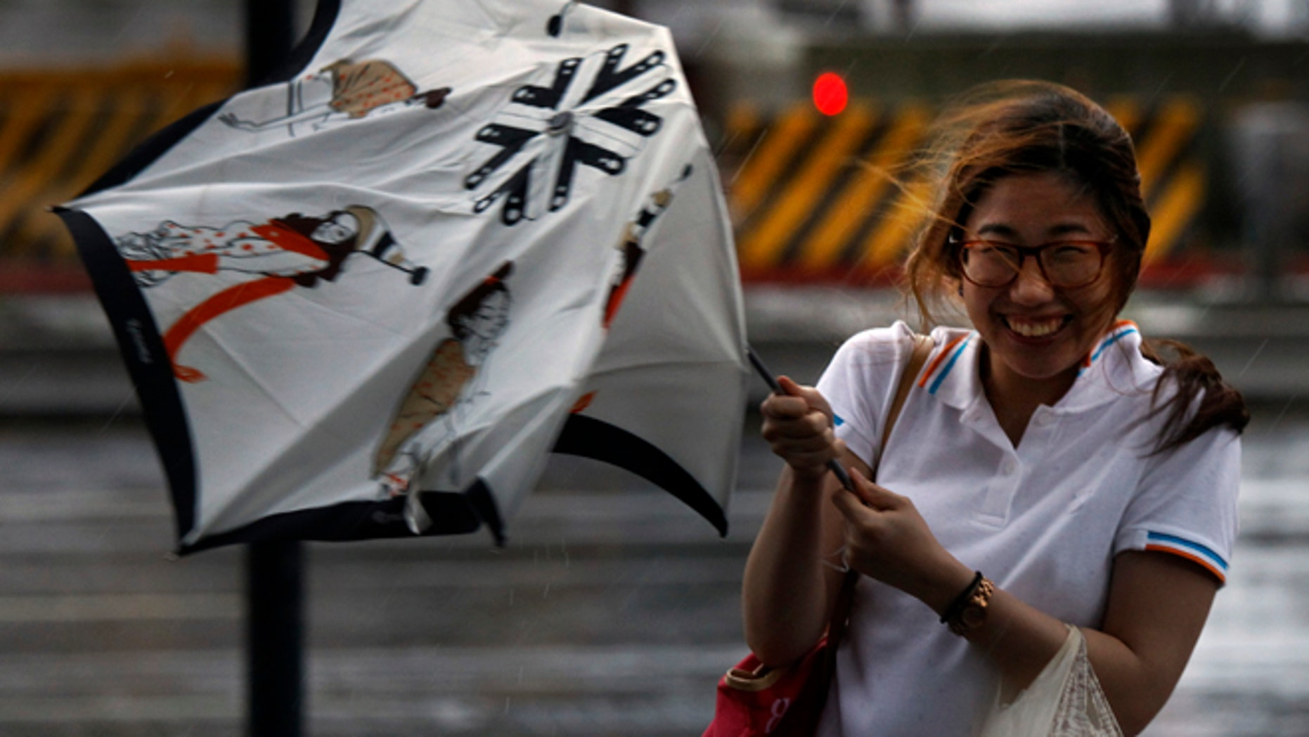 August 1, 2012: A woman reacts upon her umbrella was damaged by strong winds from an approaching typhoon in Taipei, Taiwan.