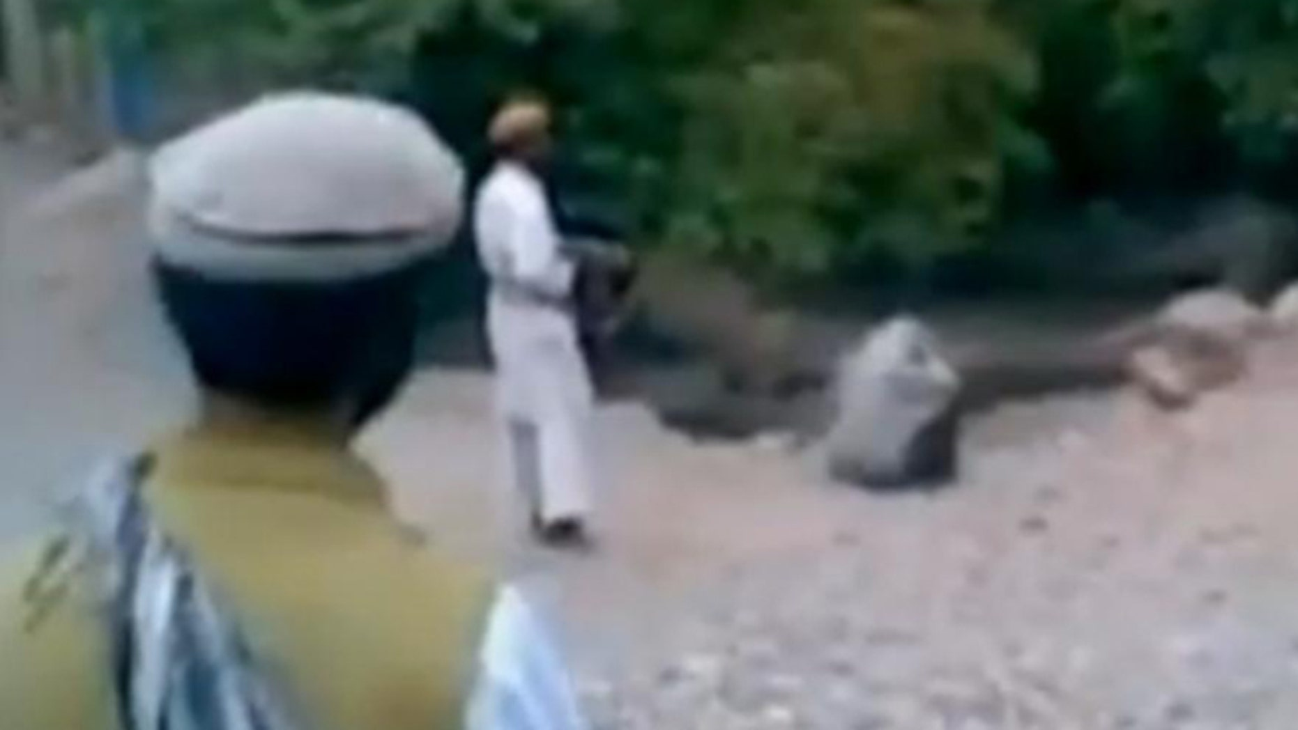 This image taken from a Reuters video allegedly shows a woman being executed by a purported member of the Taliban.
