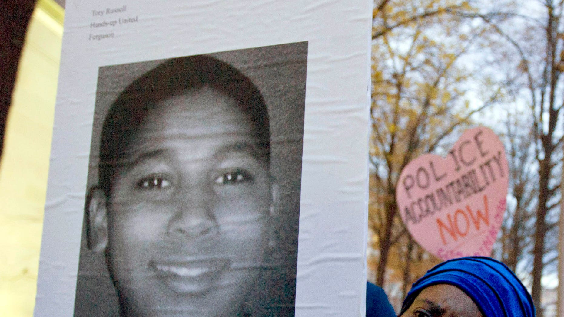 A woman holds up a picture of Tamir Rice, 12, who was fatally shot by a police officer in Cleveland, Ohio.