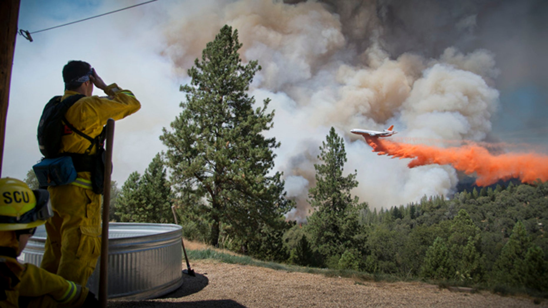 July 26, 2014: A DC-10 Air Tanker makes a drop on the Sand Fire at the middle fork of the Cosumnes River in Northern California as firefighters standby to protect a home.