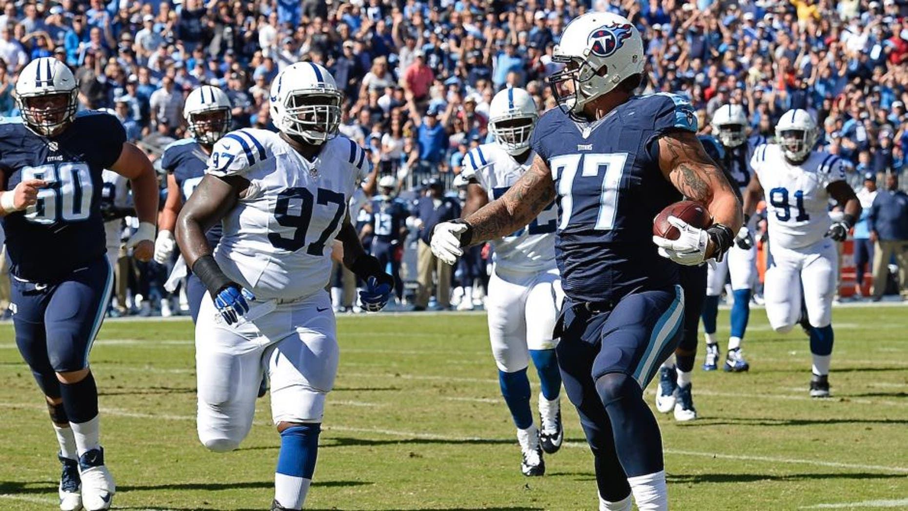 Tennessee Titans tackle Taylor Lewan (77) beats Indianapolis Colts defensive tackle Arthur Jones (97) to the end zone as Lewan scores a touchdown on a 10-yard pass play in the first half of an NFL football game Sunday, Oct. 23, 2016, in Nashville, Tenn. (AP Photo/Mark Zaleski)