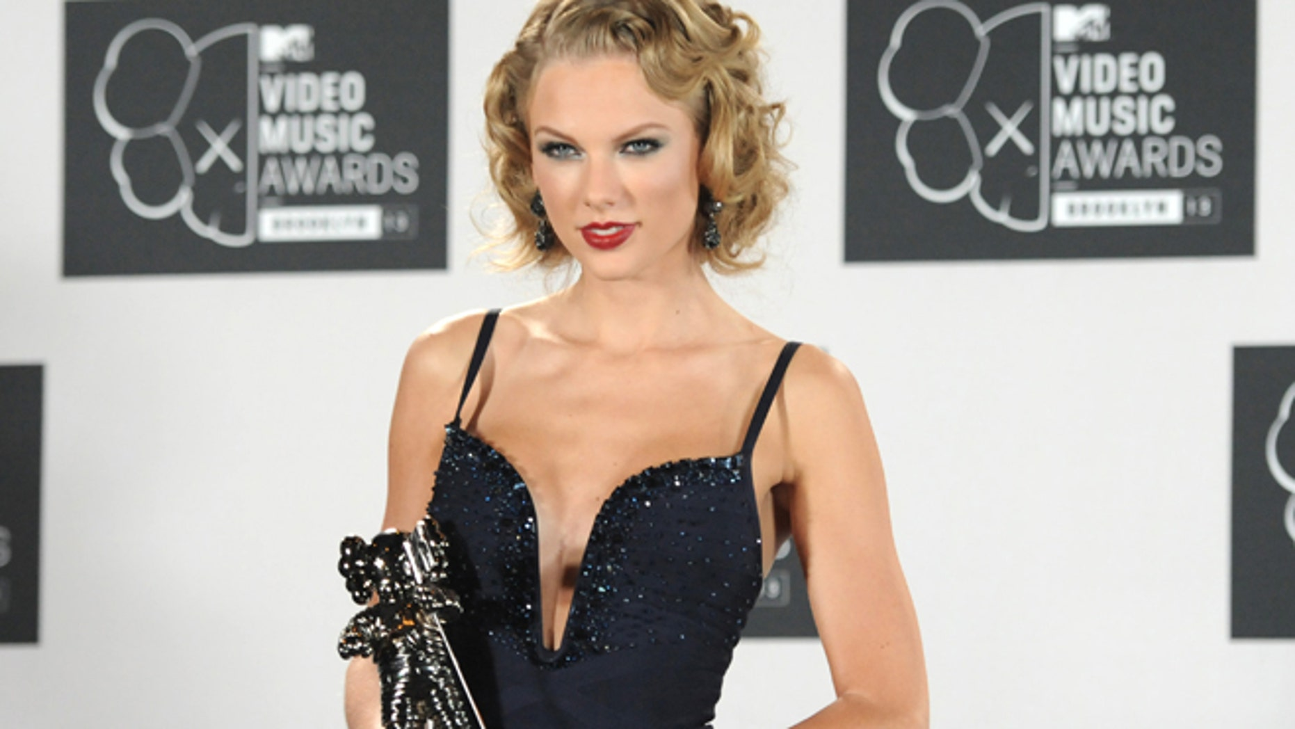 """Taylor Swift poses backstage with the award for Best Female Video for """"I Knew You Were Trouble"""" at the MTV Video Music Awards on Sunday, Aug. 25, 2013, at the Barclays Center in the Brooklyn borough of New York."""