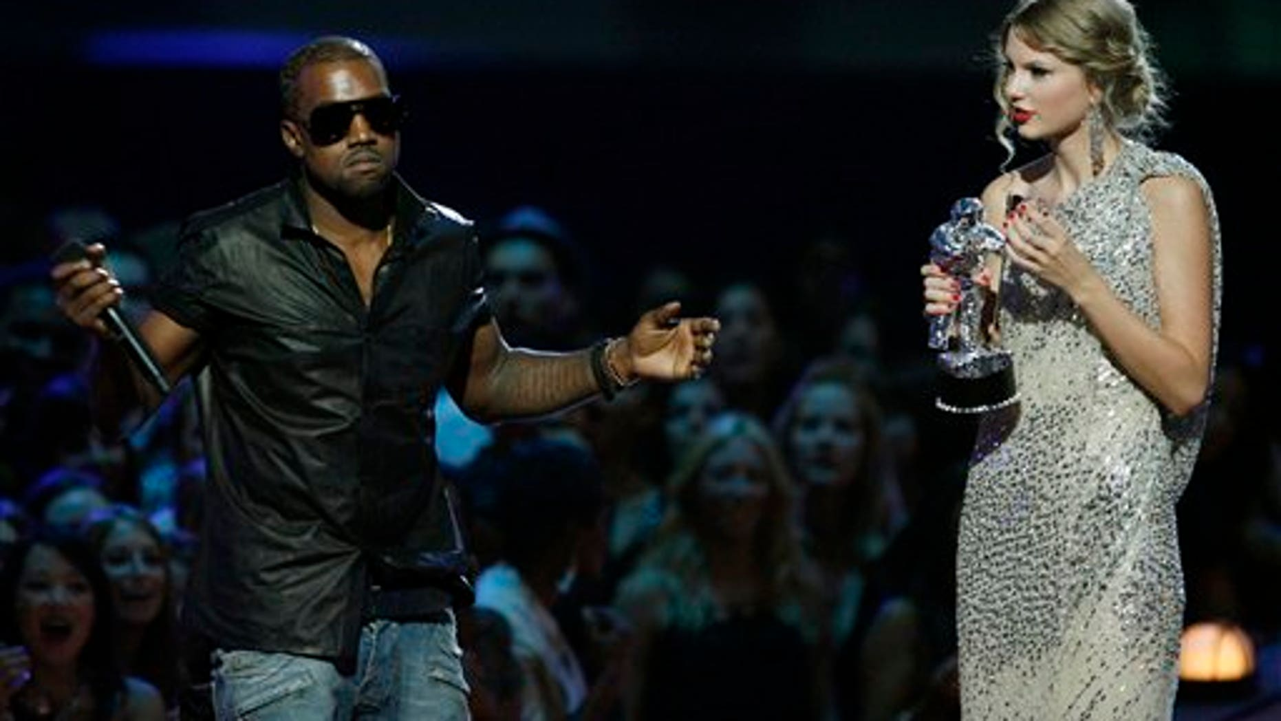 """Sept 13, 2009: Singer Kanye West takes the microphone from singer Taylor Swift as she accepts the """"Best Female Video"""" award during the MTV Video Music Awards."""