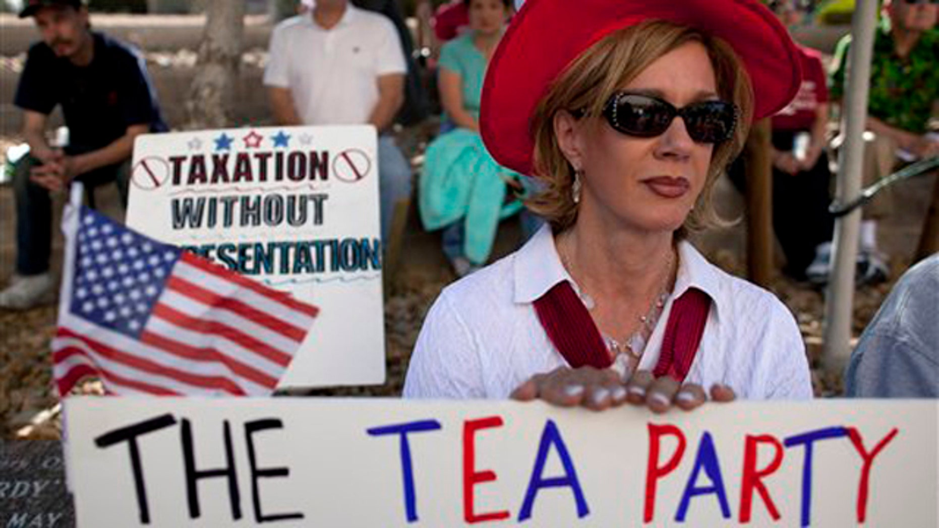 In this April 15 file photo, an activist in Las Vegas listens to speakers during a Tea Party rally.