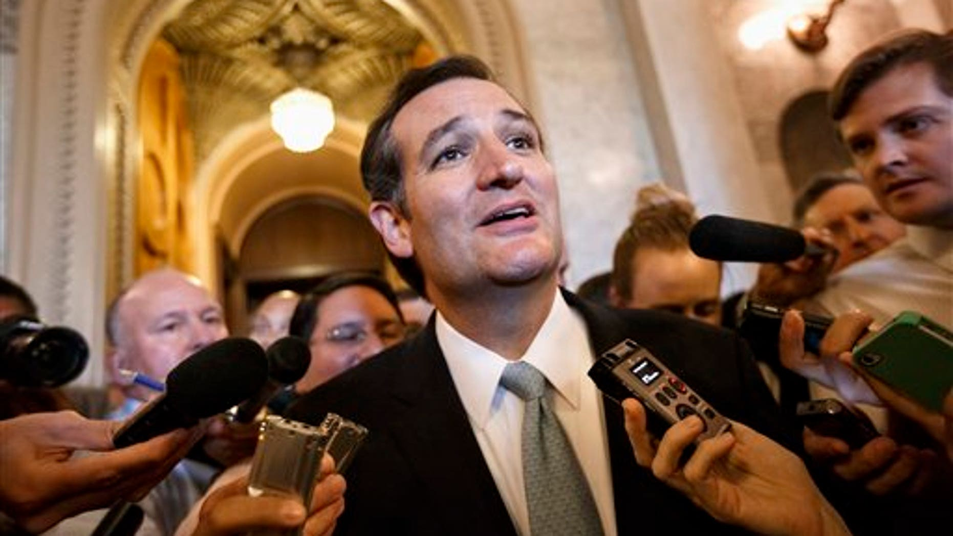Sen. Ted Cruz talks to reporters as he emerges from the Senate Chamber on Capitol Hill in Washington, Wednesday, Sept 25, 2013.