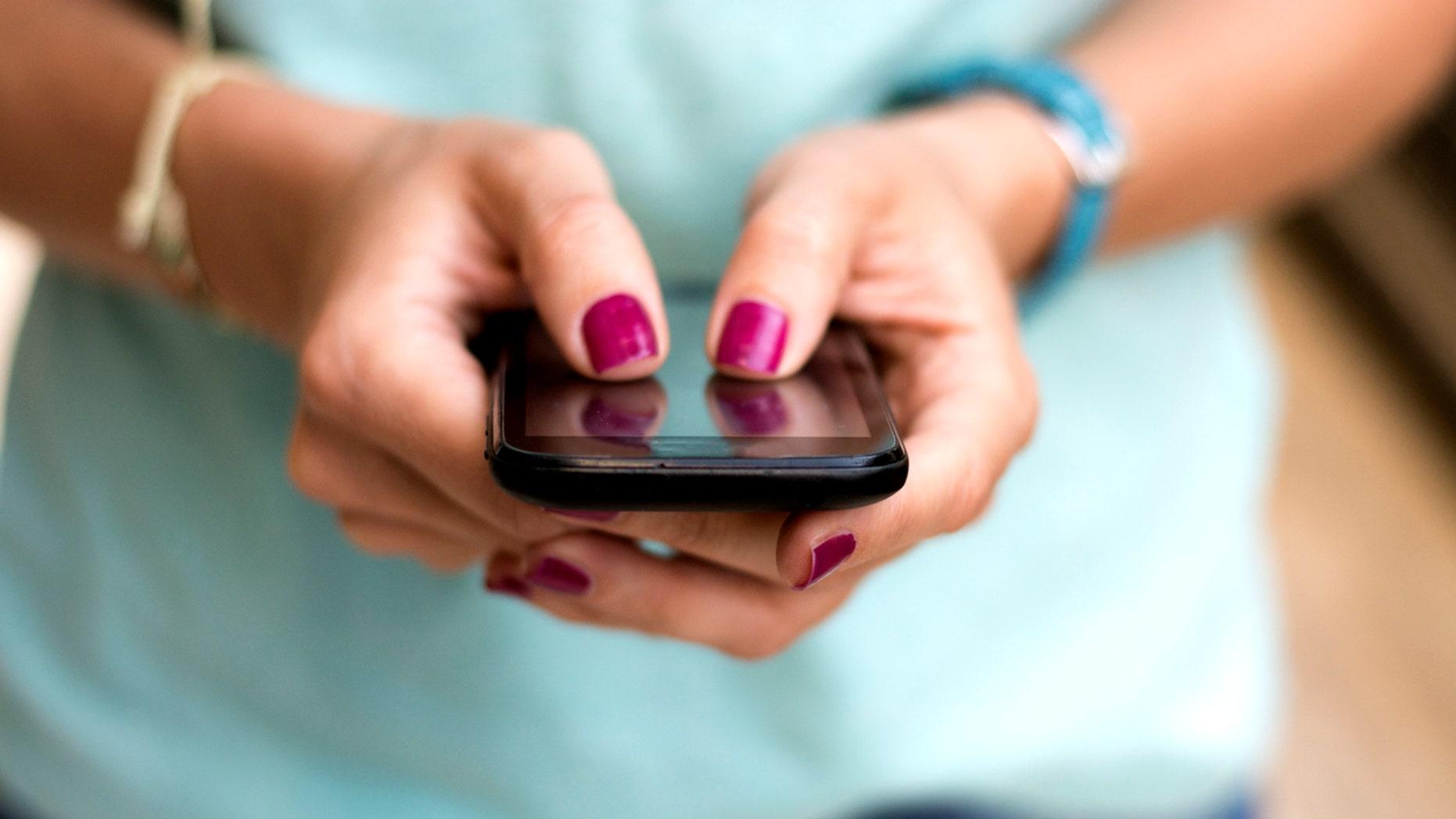 Girl holding smart phone outside