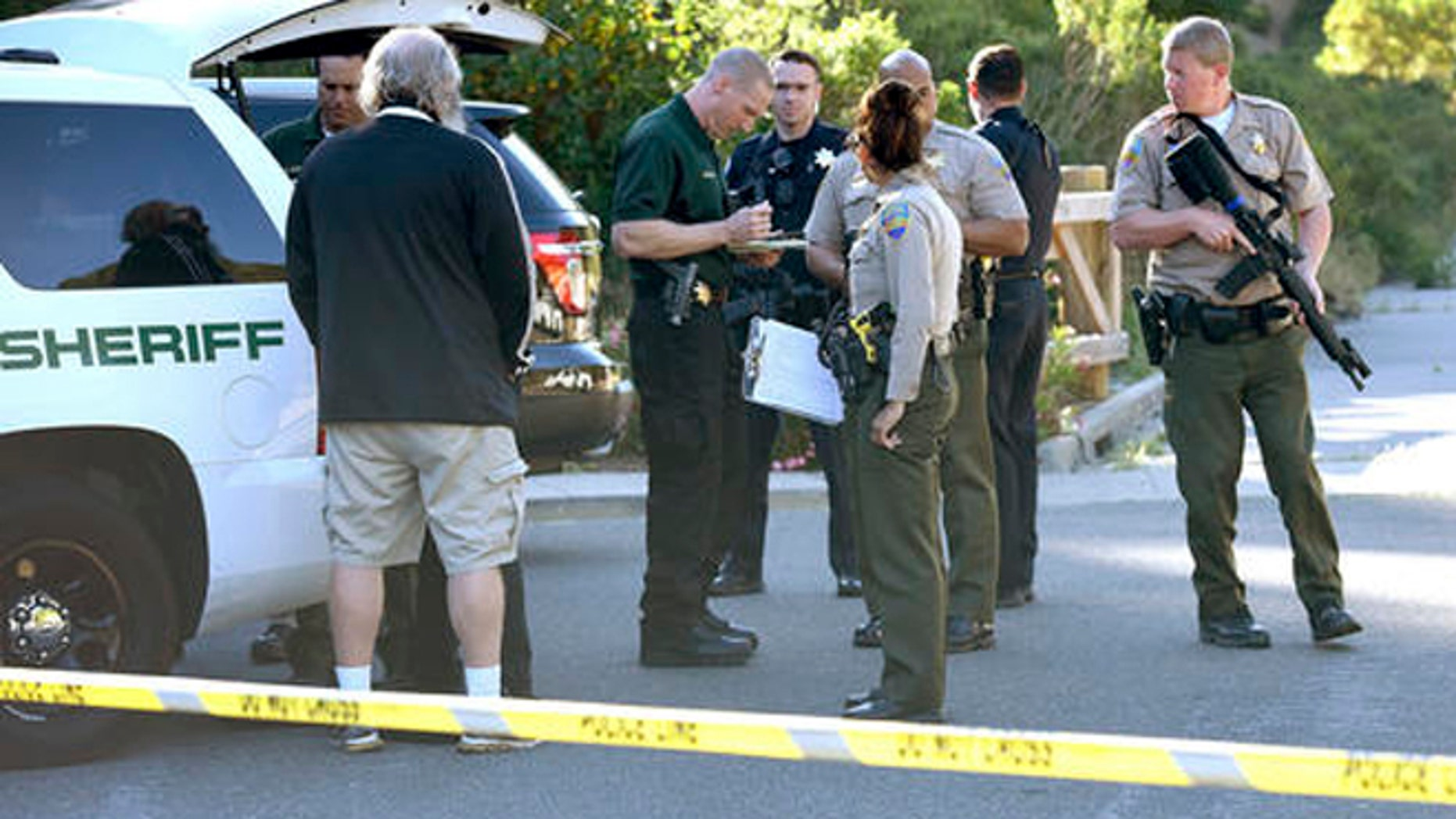 In this photo taken Wednesday, May 25, 2016, Marin County Sheriff and Novato police members gather at a command post to form a massive manhunt following at attack on two students in Novato, Calif. Attackers shot two students near a San Francisco Bay Area high school, killing one and sending another to a hospital in an incident that prompted the closing of the campus, authorities said Thursday. Both victims were students at Novato High School. (Robert Tong/Marin Independent Journal via AP)