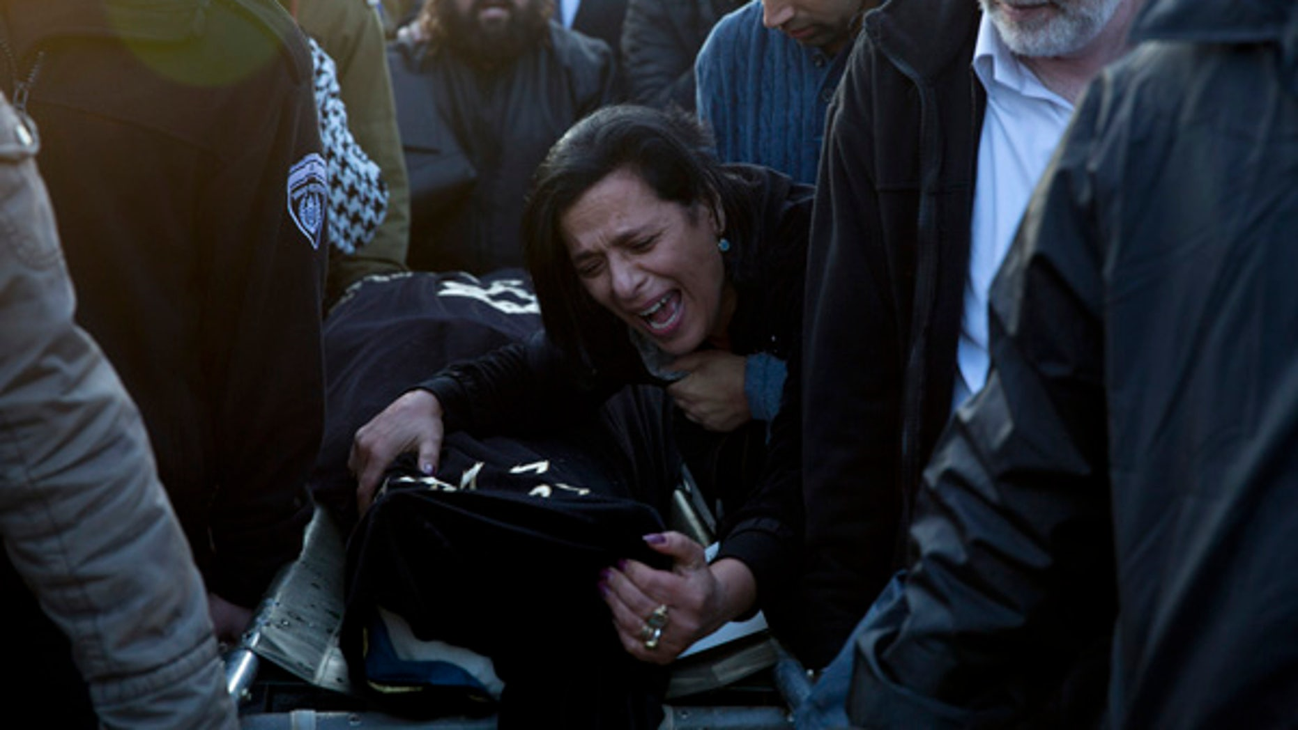 Jan. 3, 2016: Nitza Bakal, mother of Alon Bakal, center, who was killed when a gunman opened fire at a bar in Tel Aviv on Friday, mourn over his body during his funeral in Carmiel, northern Israel.