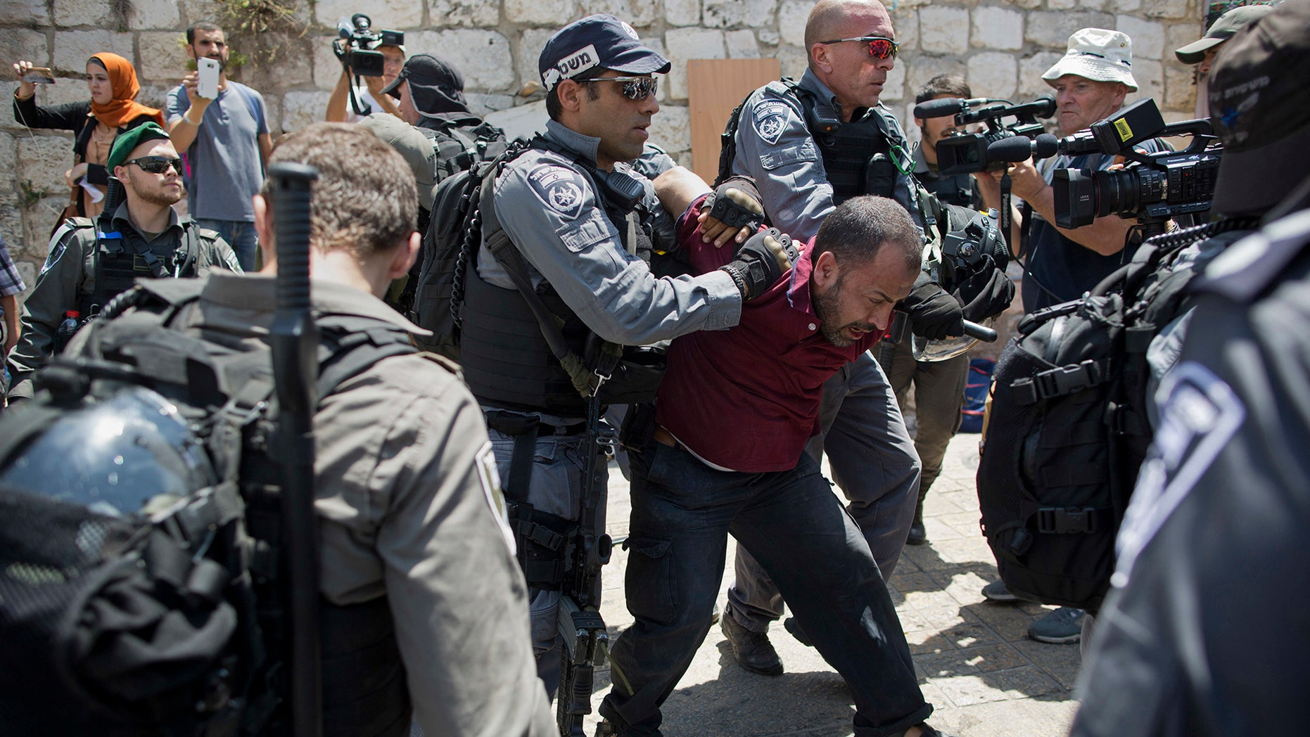 Israeli police officers detain a Palestinian man outside the Lion's Gate, following an appeal from clerics to pray in the streets instead of the Al Aqsa Mosque compound, in Jerusalem's Old City, Wednesday, July 19, 2017.