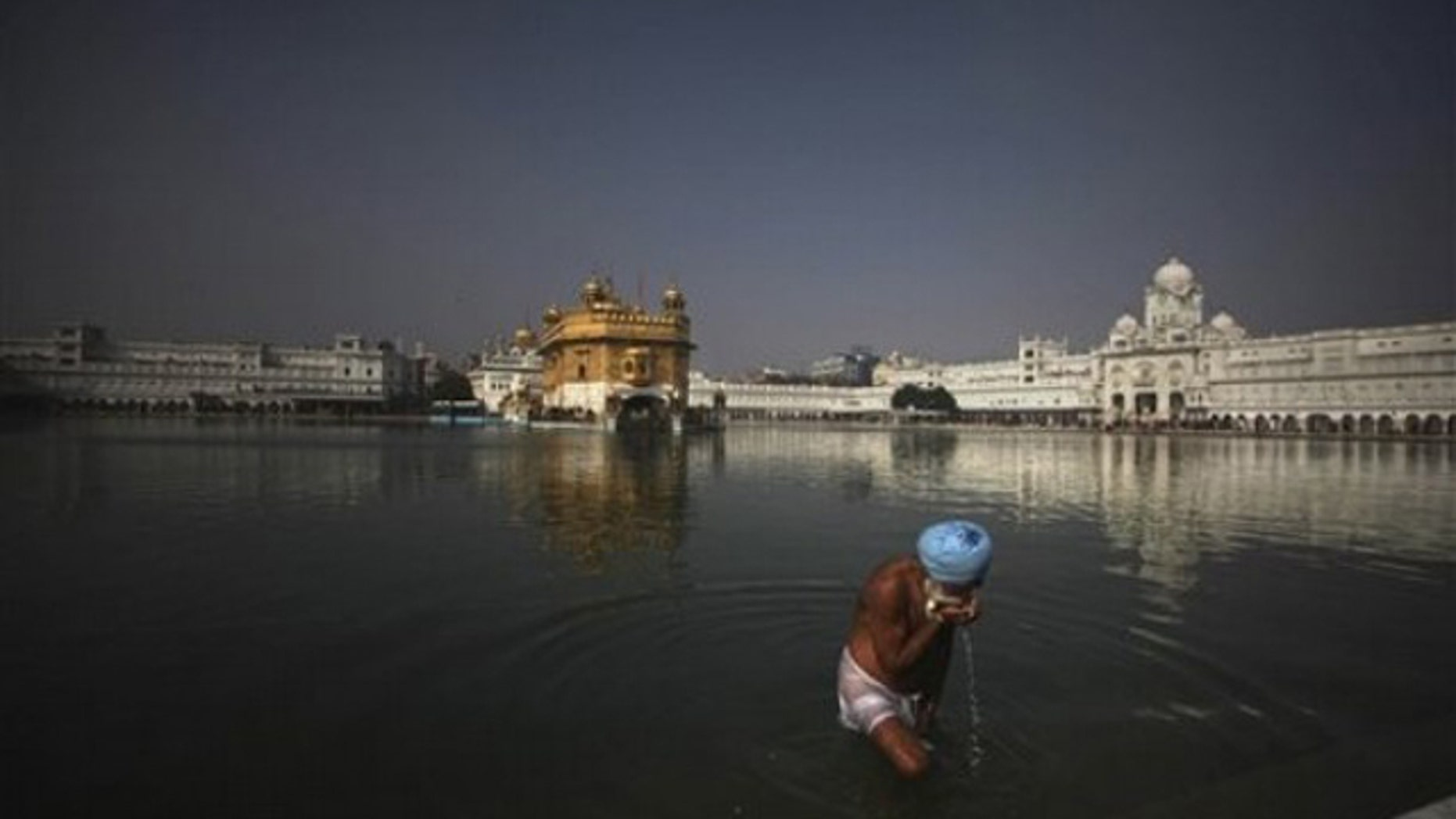 A Sikh devotee drinks water from the holy pond at the Golden Temple in Amritsar, India, on Jan. 4. (AP Photo)