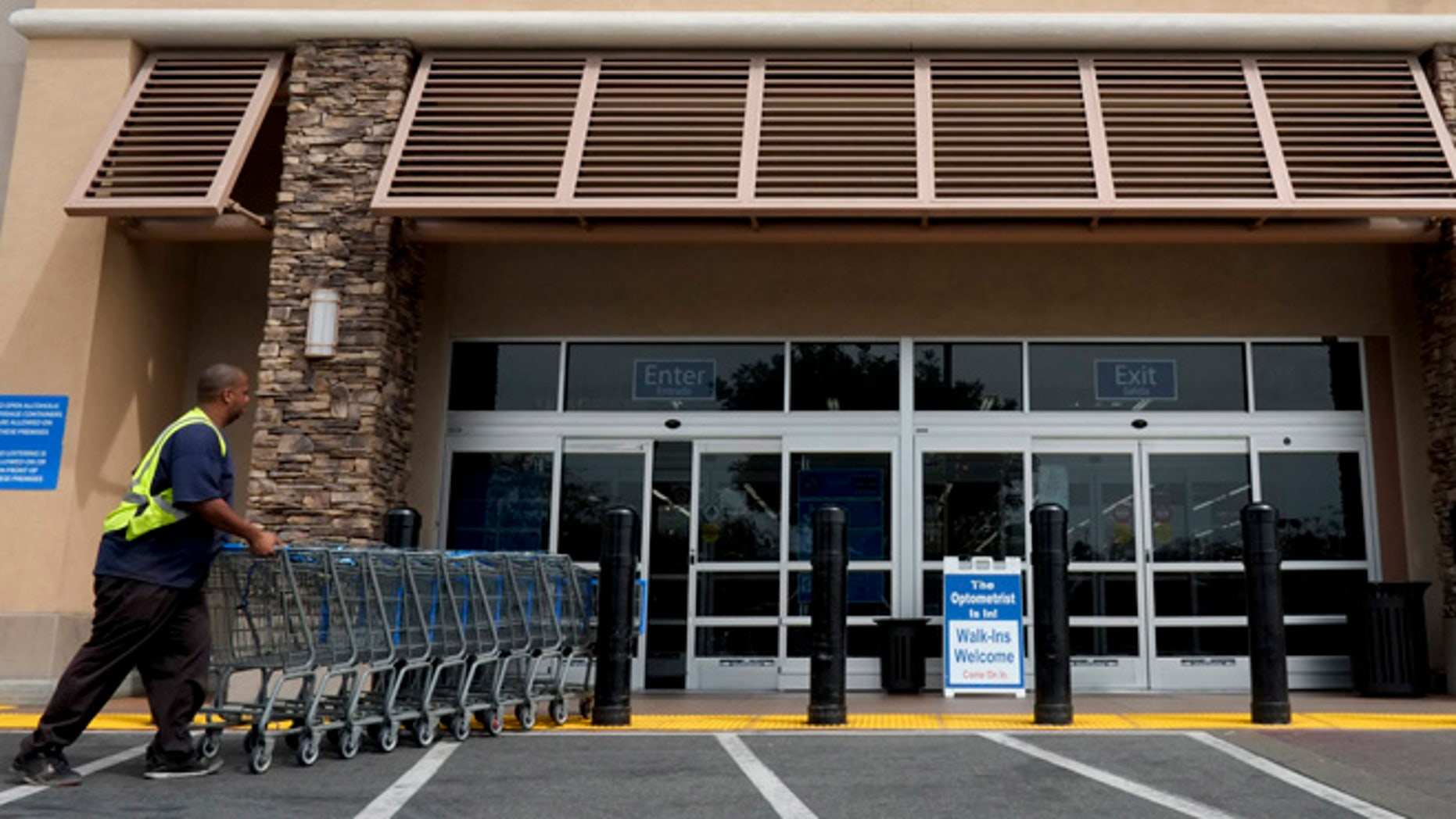 In this May 9, 2013 file photo, a worker pushes shopping carts in front of a Wal-Mart store in La Habra, Calif. From Wal-Mart to General Motors to PepsiCo, companies are increasingly turning to temporary workers and to a much larger universe of freelancers, contract workers and consultants.