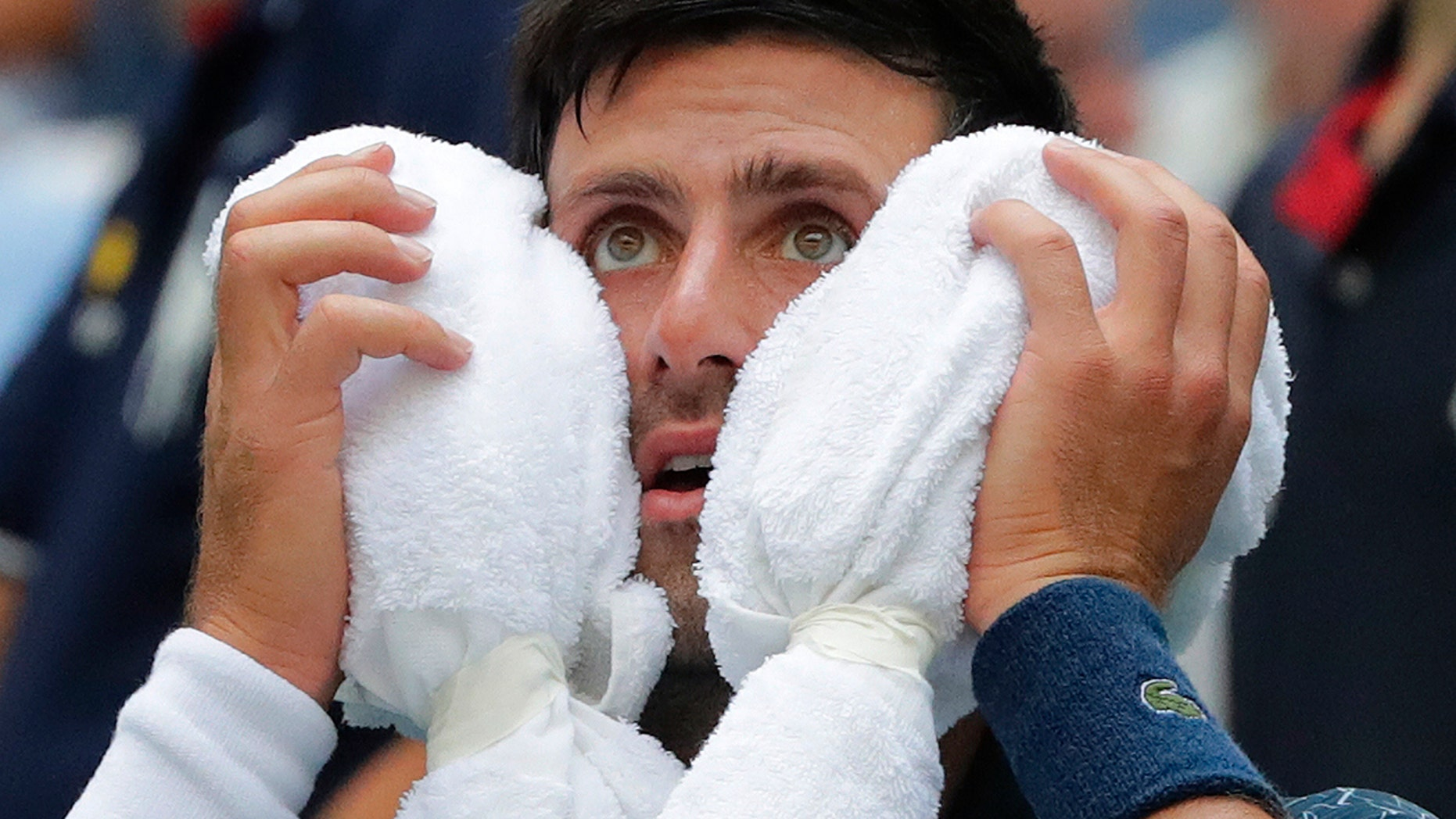 Novak Djokovic, of Serbia, puts an ice towel to his face during a changeover in his match against Marton Fucsovics, of Hungary, during the first round of the U.S. Open tennis tournament.