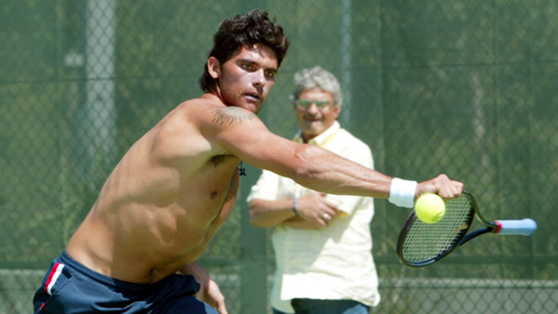 Mark Philippoussis of Australia plays at the ball with the handle of his racket as his father Nick looks on during practice at the Sydney International Tennis Center in January 2004.