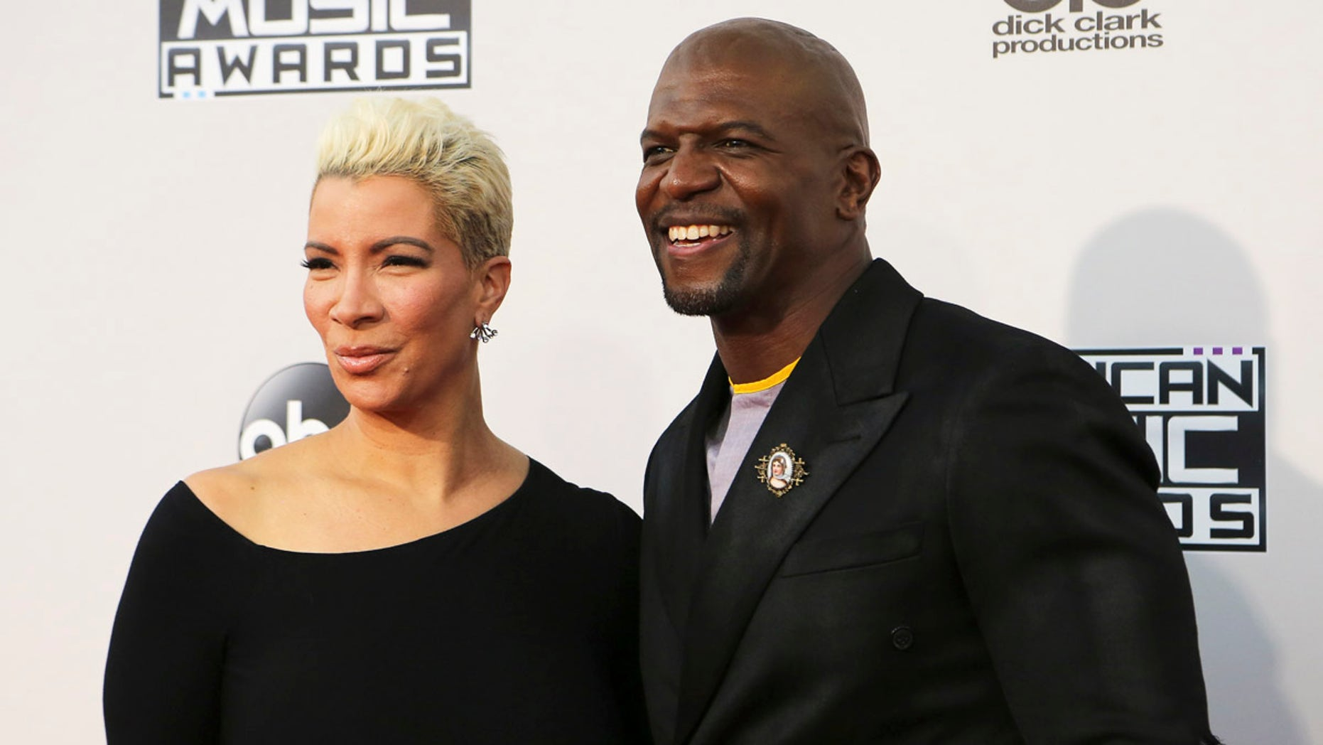 Actor Terry Crews and his wife, Rebecca King-Crews, arrive at the 2015 American Music Awards in Los Angeles, Nov. 22, 2015.