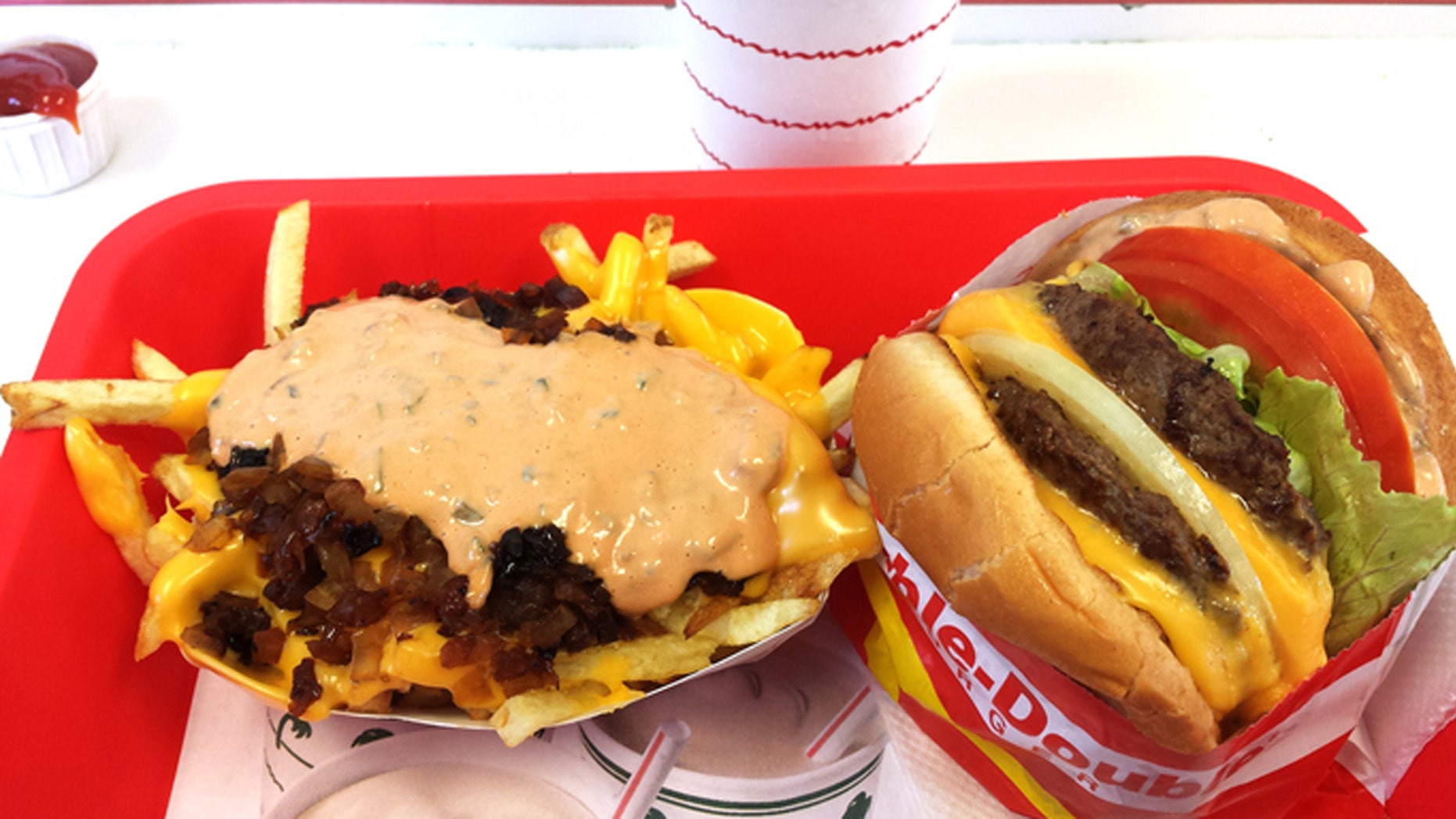 "Los Angeles, California, USA - August 20, 2015: In-N-Out Burgers, Inc. is a regional chain of fast food restaurants that started in California. Two of their most popular menu items are the ""Double-Double"" hamburger - two hamburger patties with two slices of cheese, and the ""Animal Style"" french fries - two slices of melted cheese, spread, and grilled onions on top."