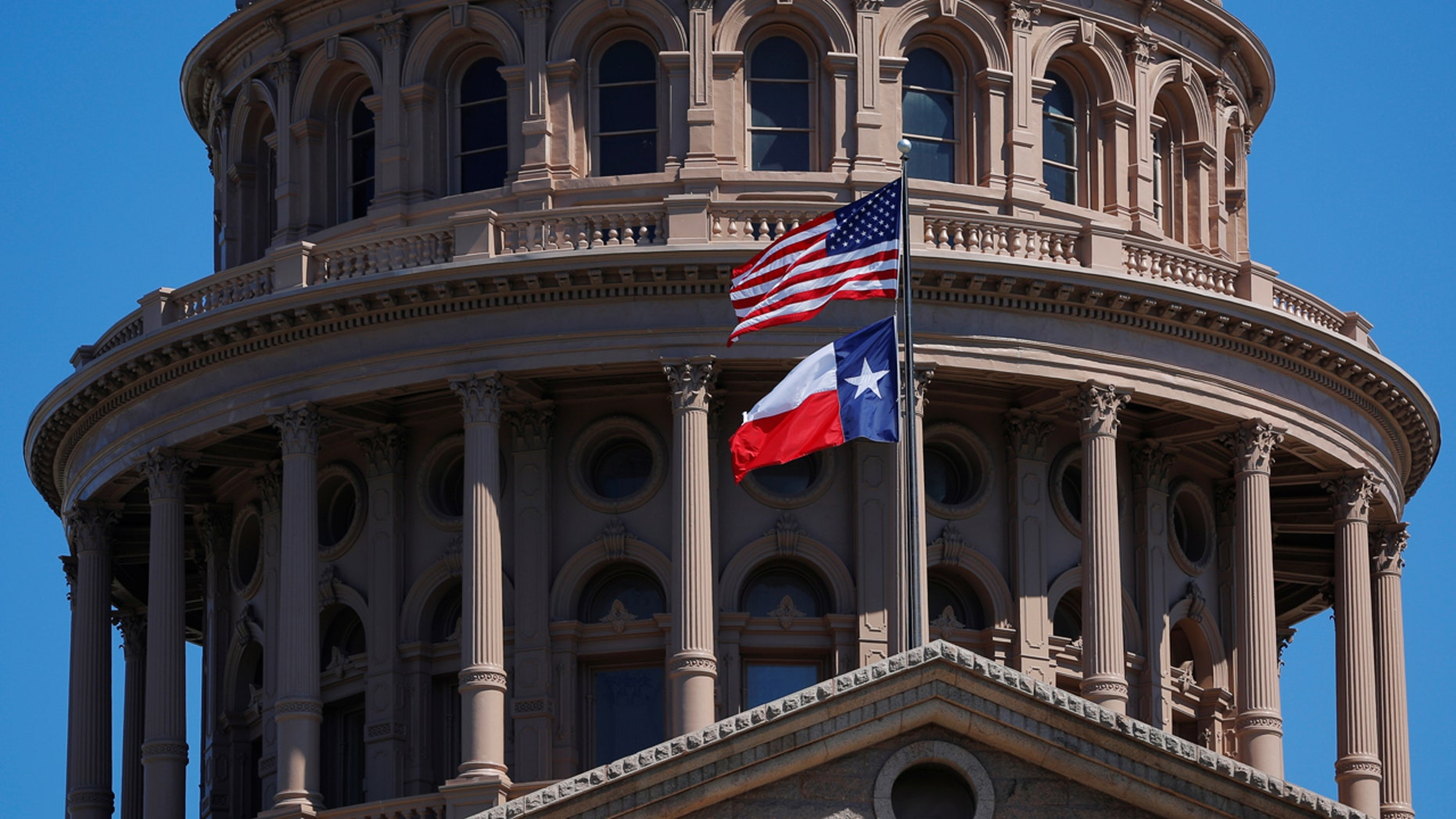 The American flag and the Texas state fly over the Texas State Capitol in Austin, March 14, 2017.