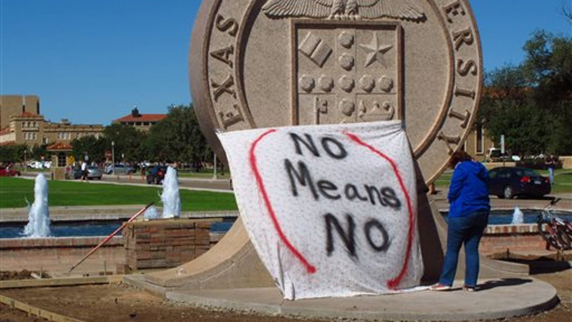 """FILE - In this Wednesday, Oct. 1, 2014 file photo, Texas Tech freshman Regan Elder helps drape a bed sheet with the message """"No Means No"""" over the university's seal at the Lubbock, Texas campus to protest what students say is a """"rape culture"""" on campus. (AP Photo/Betsy Blaney)"""