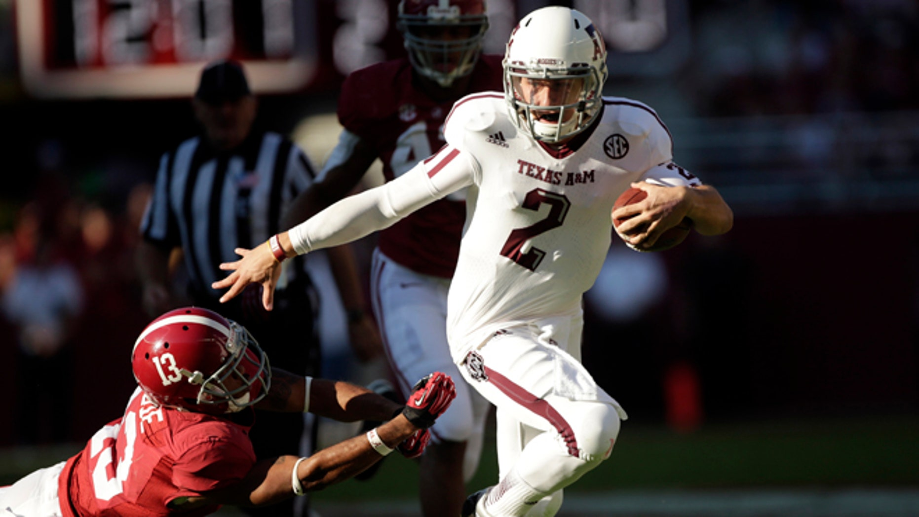 Nov. 10, 2012: Texas A&M quarterback Johnny Manziel (2) runs through the tackle of Alabama defensive back Deion Belue (13) during the first half of an NCAA college football game at Bryant-Denny Stadium in Tuscaloosa, Ala.
