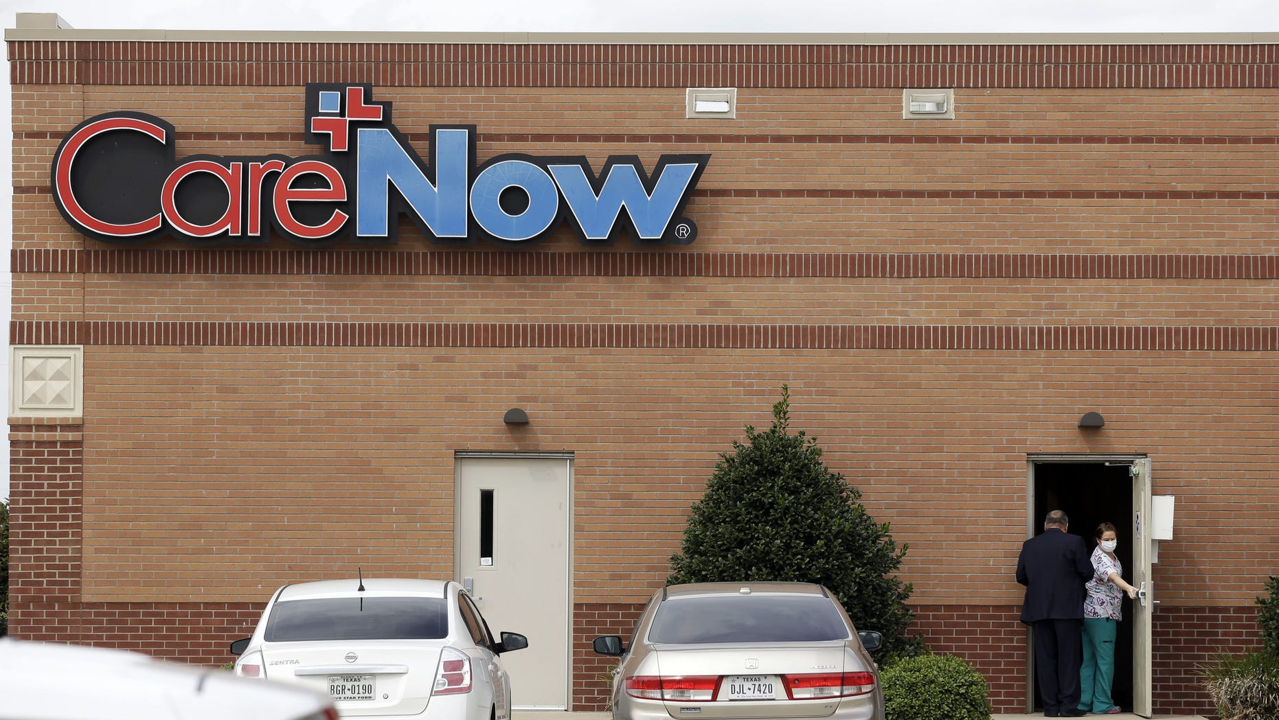 Oct. 8, 2014: A masked worker opens a door at a CareNow clinic in Frisco, Texas.
