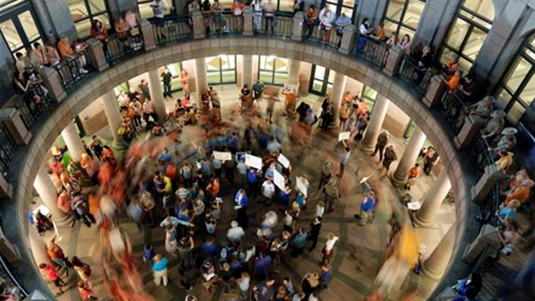 July 2, 2013: Opponents of an abortion bill walk in circles around supporters of the bill as a committee holds hearings on the bill near by at the Texas state capitol in Austin, Texas.