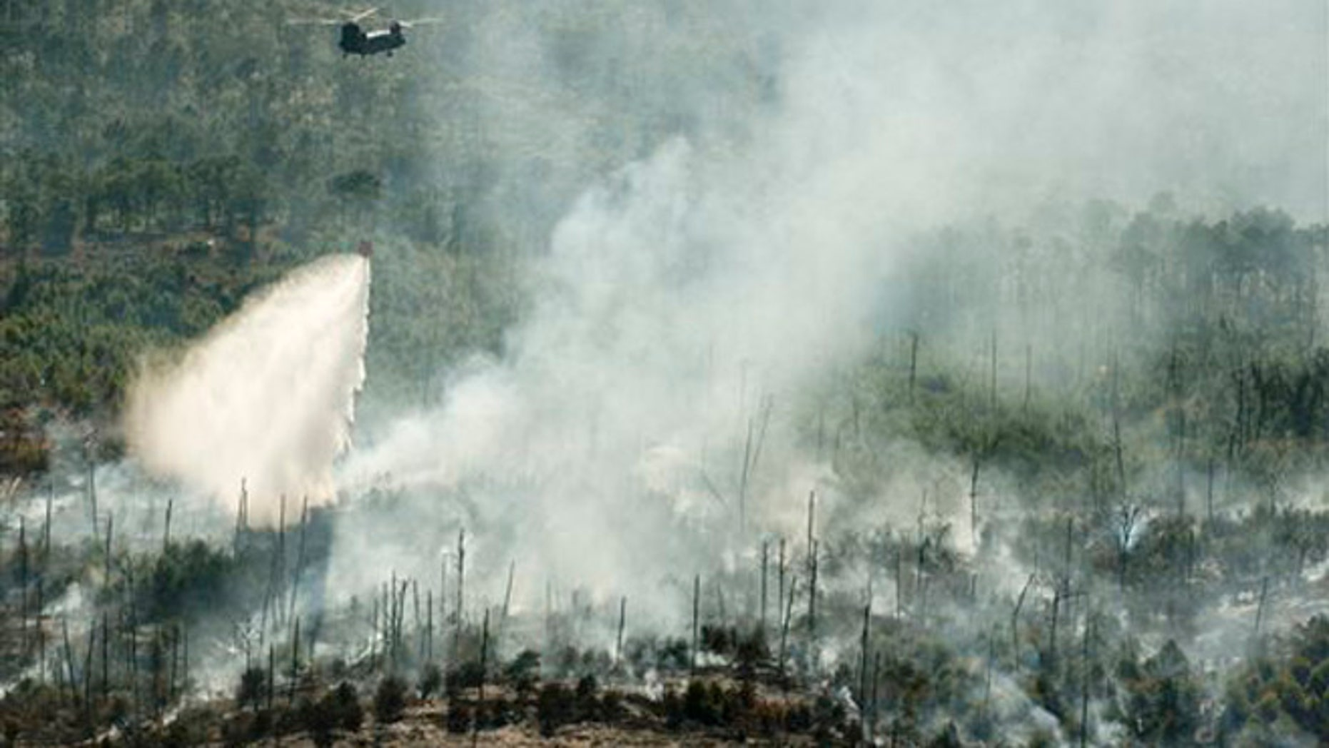 Oct 16, 2015: A helicopter drops water on the Hidden Pines Fire in Smithville, Texas.