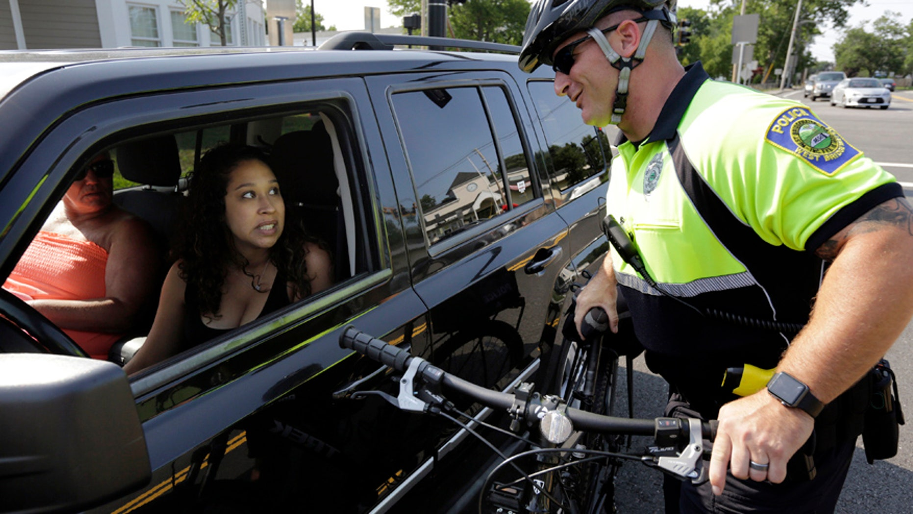 July 20, 2016: Police officer Matthew Monteiro speaks to a motorist about texting while driving while patrolling on his bicycle in East Bridgewater, Mass.